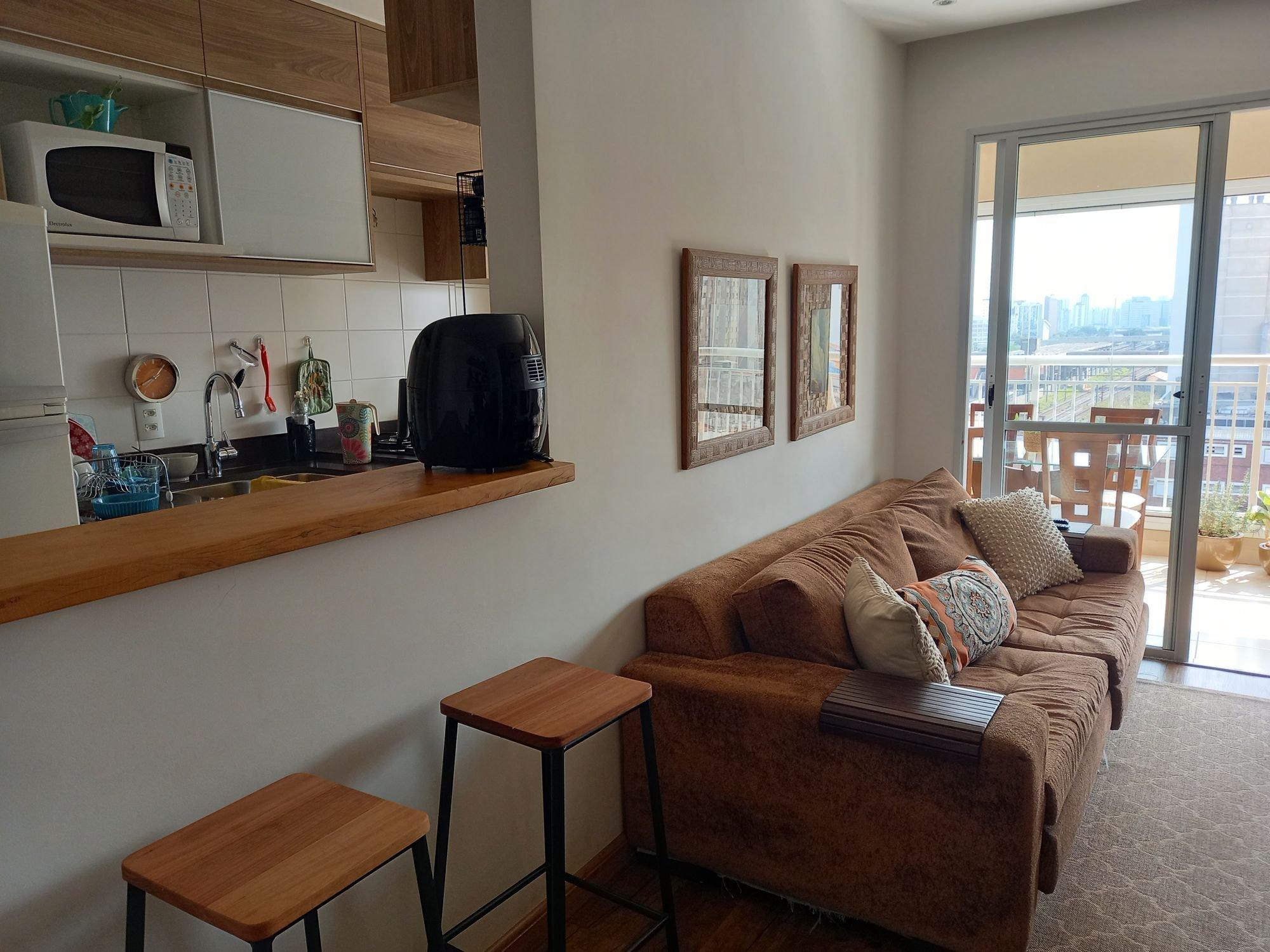 Foto de Sala com sofá, banco, microondas, xícara