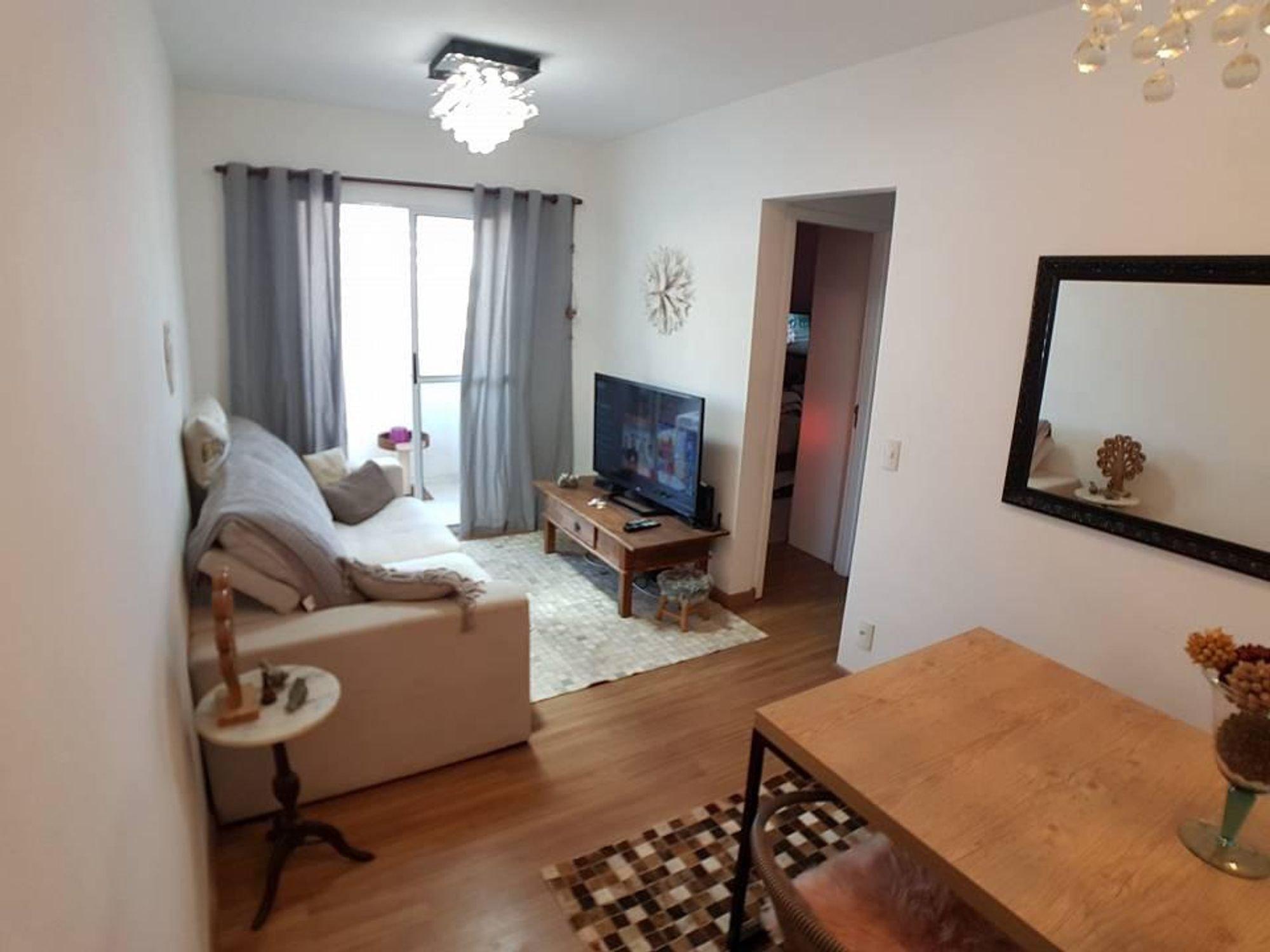 Foto de Sala com sofá, televisão, vaso, relógio, mesa de jantar