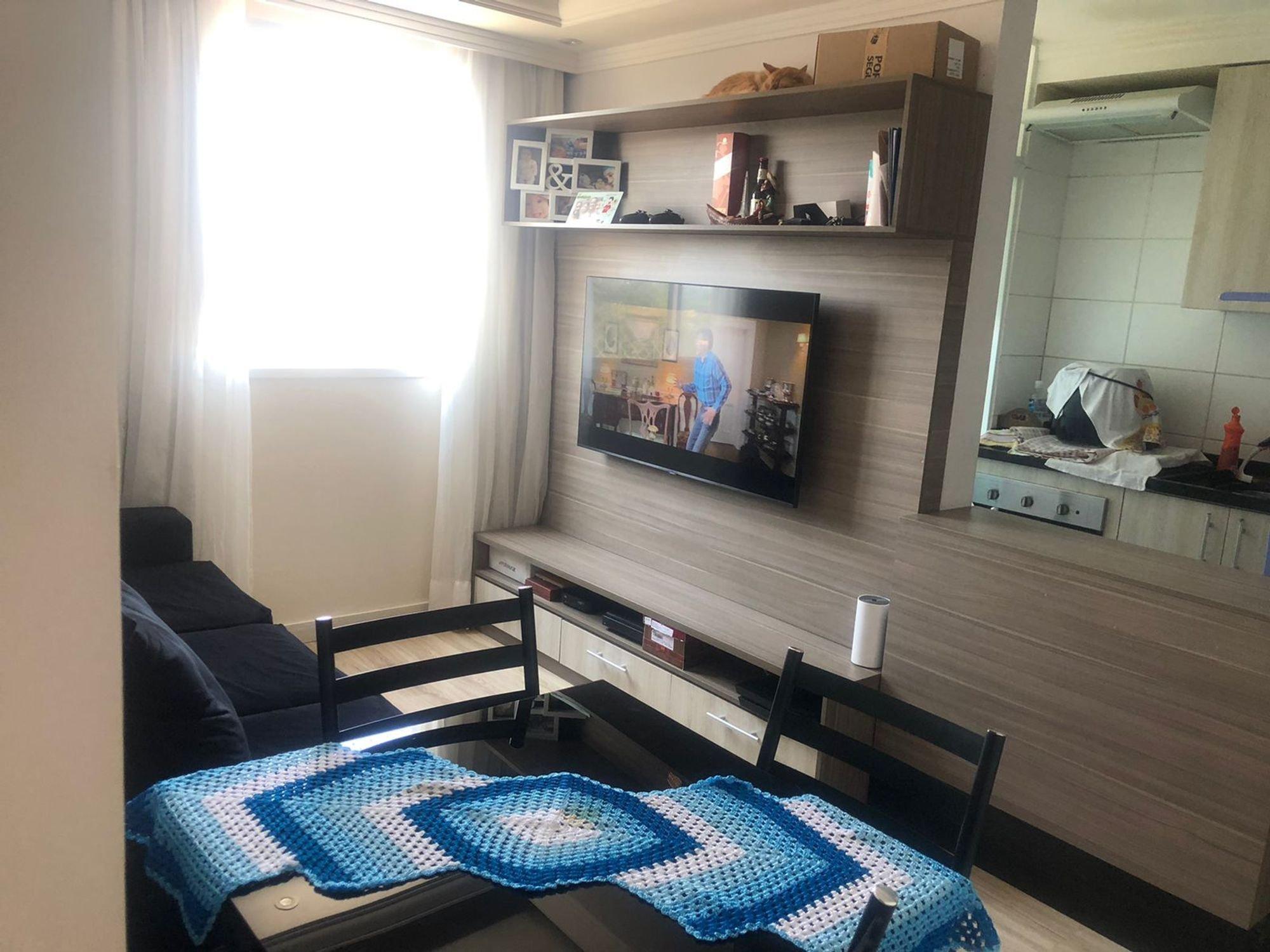 Foto de Sala com cama, televisão, garrafa, cadeira