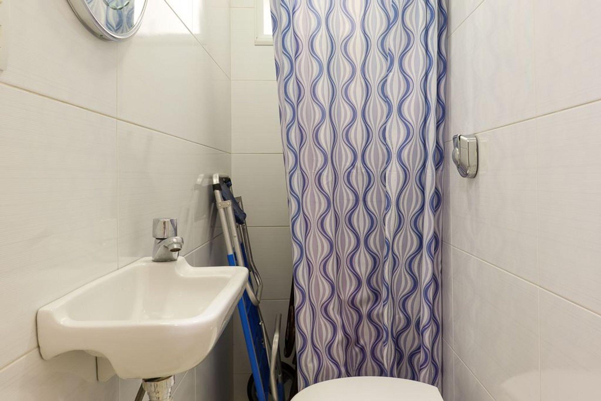 Foto de Banheiro com vaso sanitário, pia, relógio
