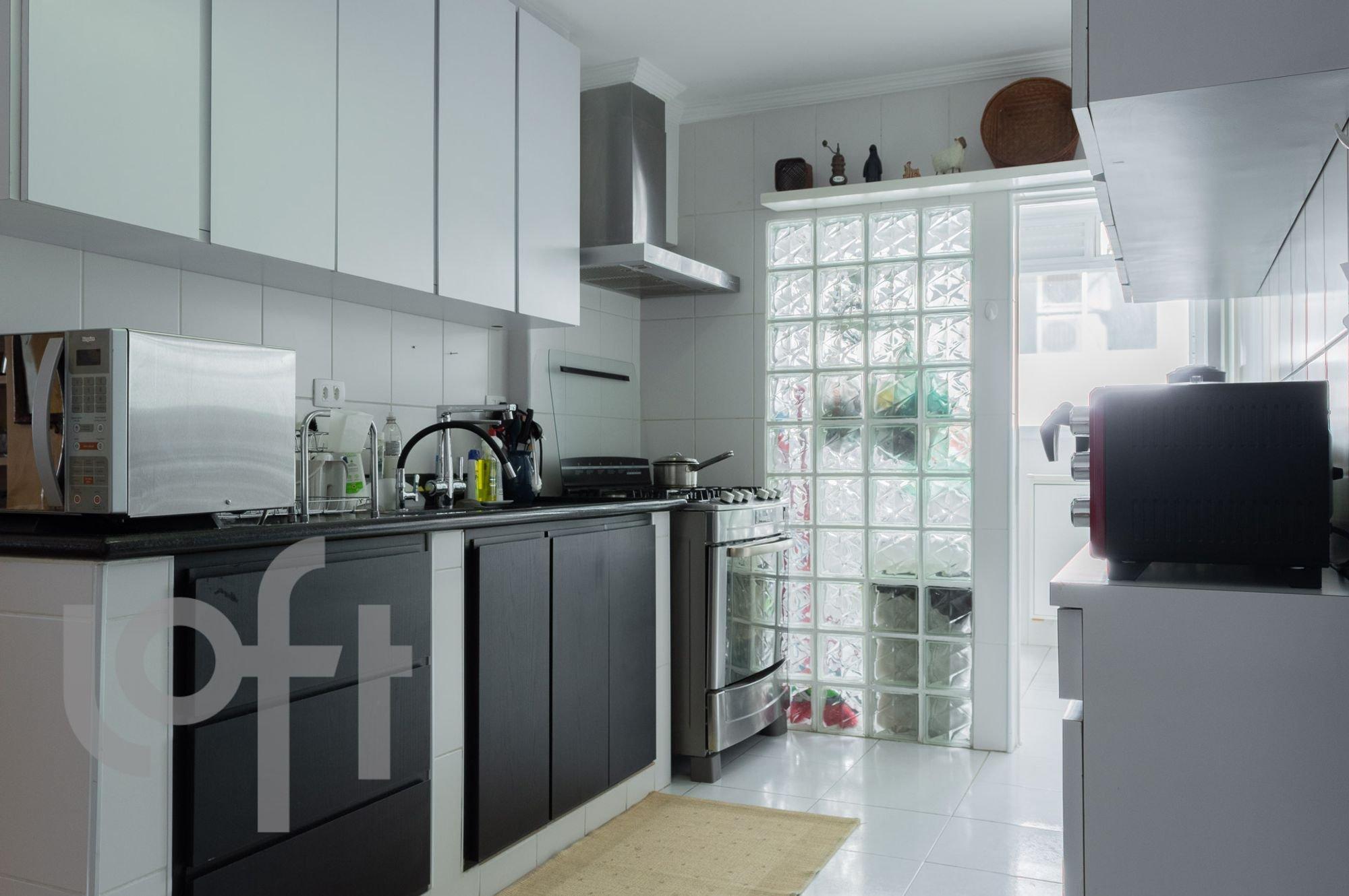 Foto de Cozinha com faca, vaso, garrafa, forno, microondas