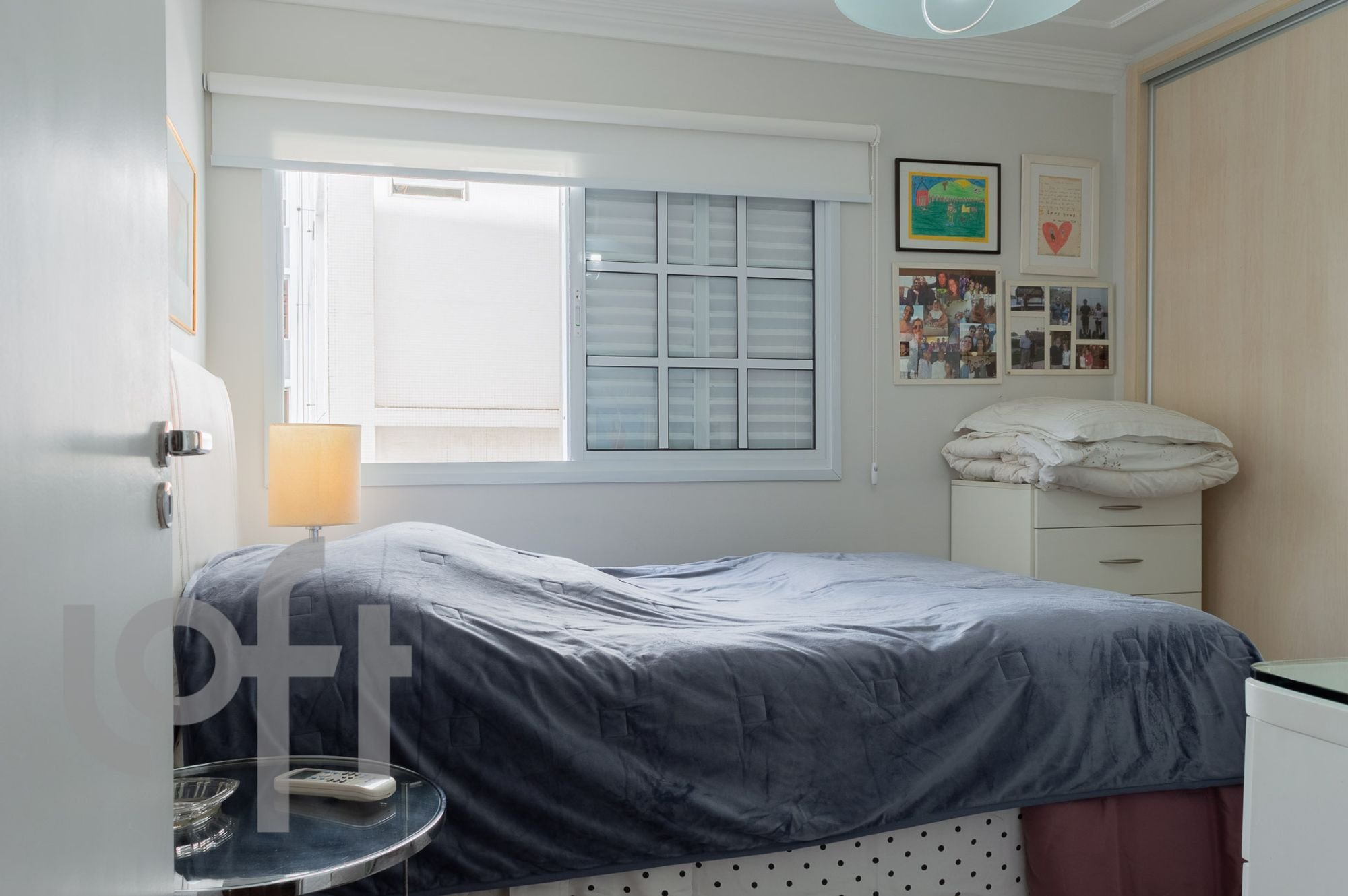 Foto de Quarto com cama, controle remoto