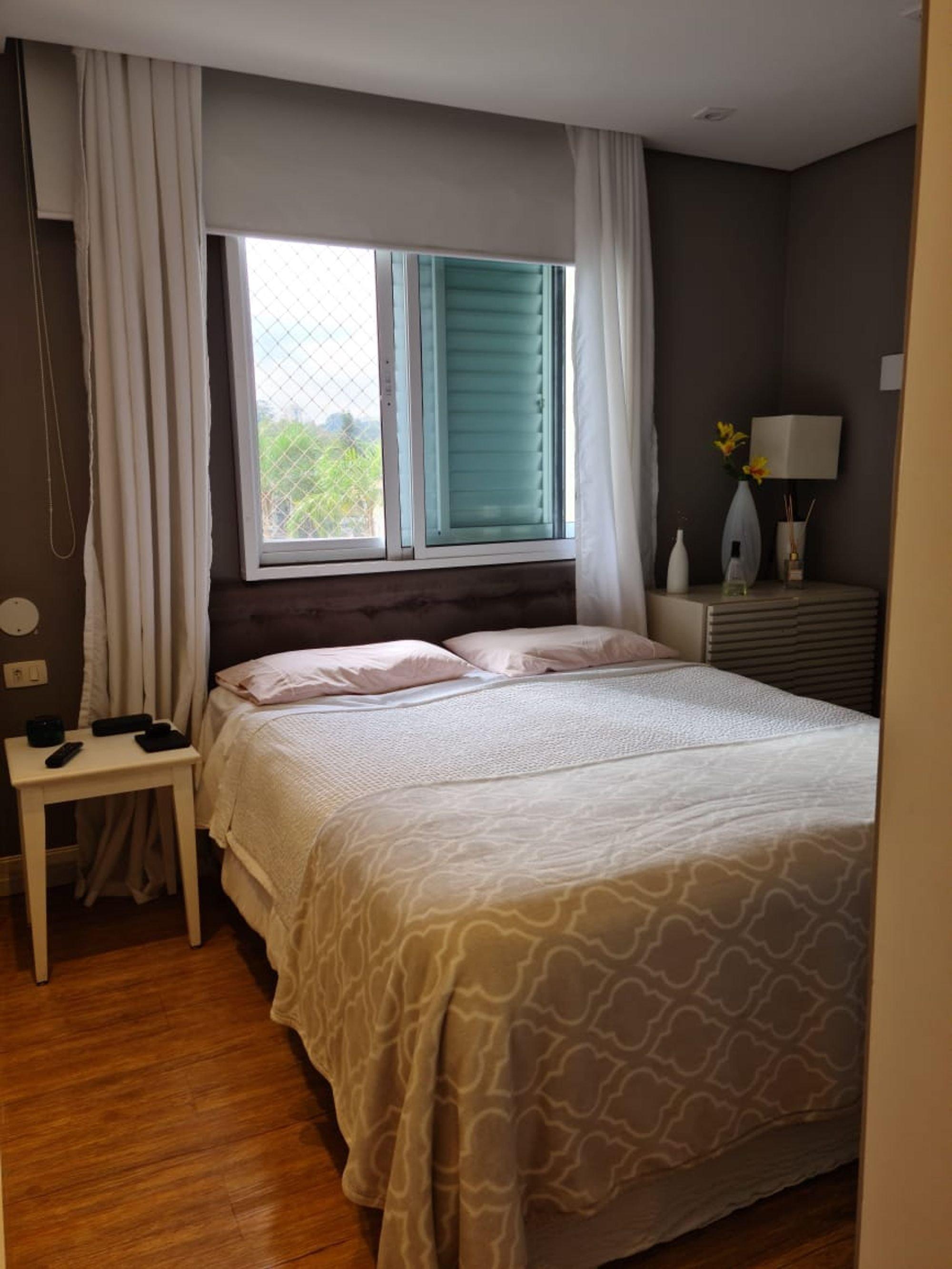 Foto de Quarto com cama, vaso, garrafa, controle remoto, mesa de jantar