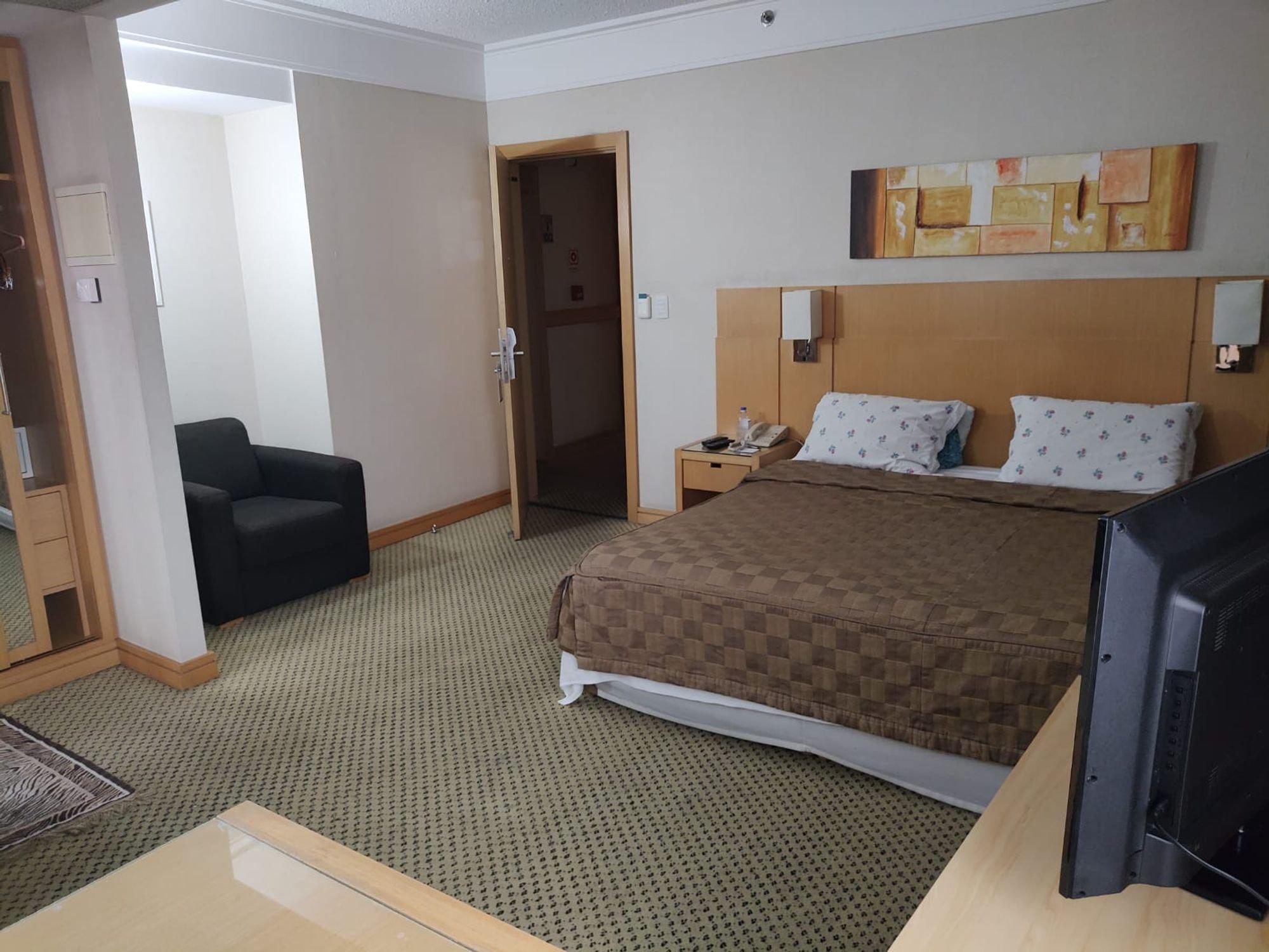 Foto de Quarto com cama, televisão, garrafa, cadeira