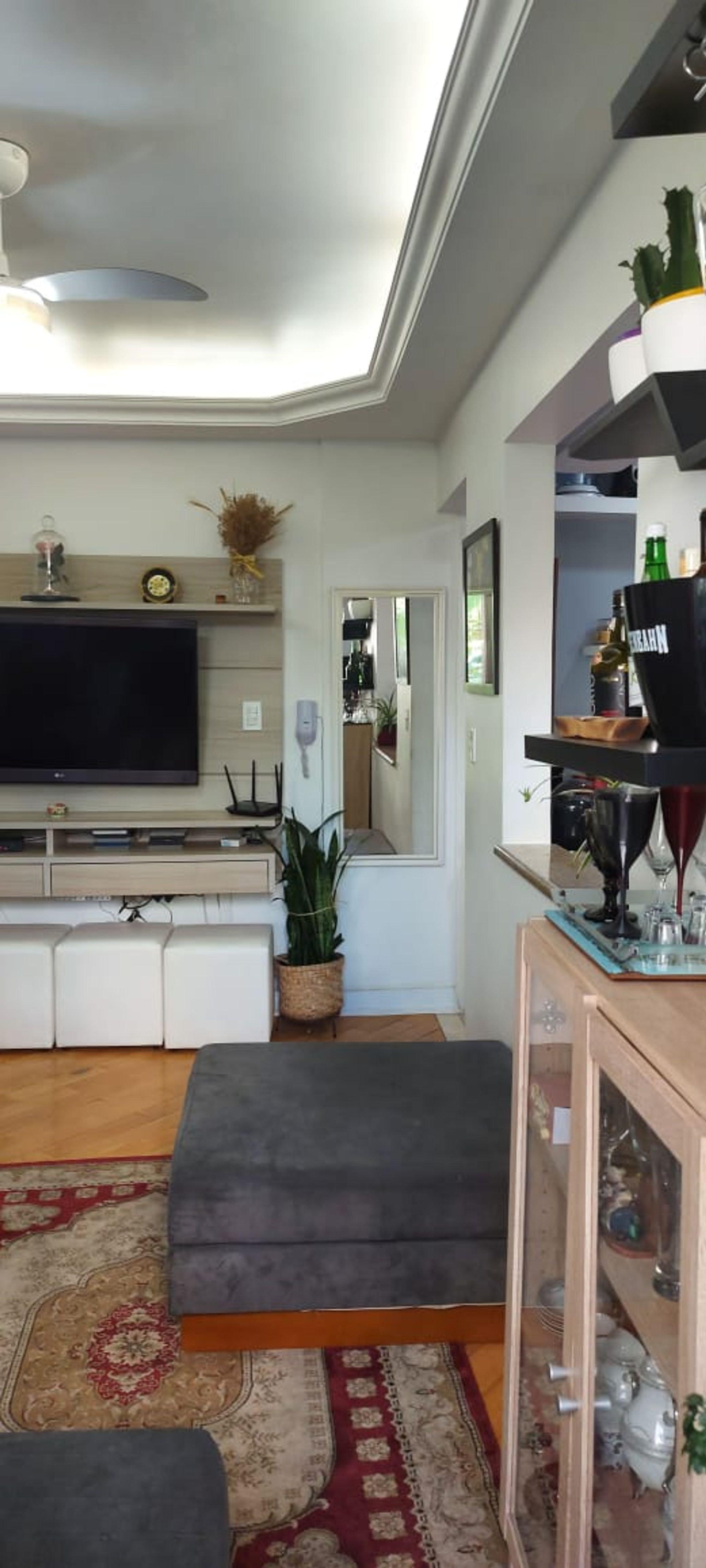 Foto de Sala com vaso de planta, televisão, relógio, garrafa