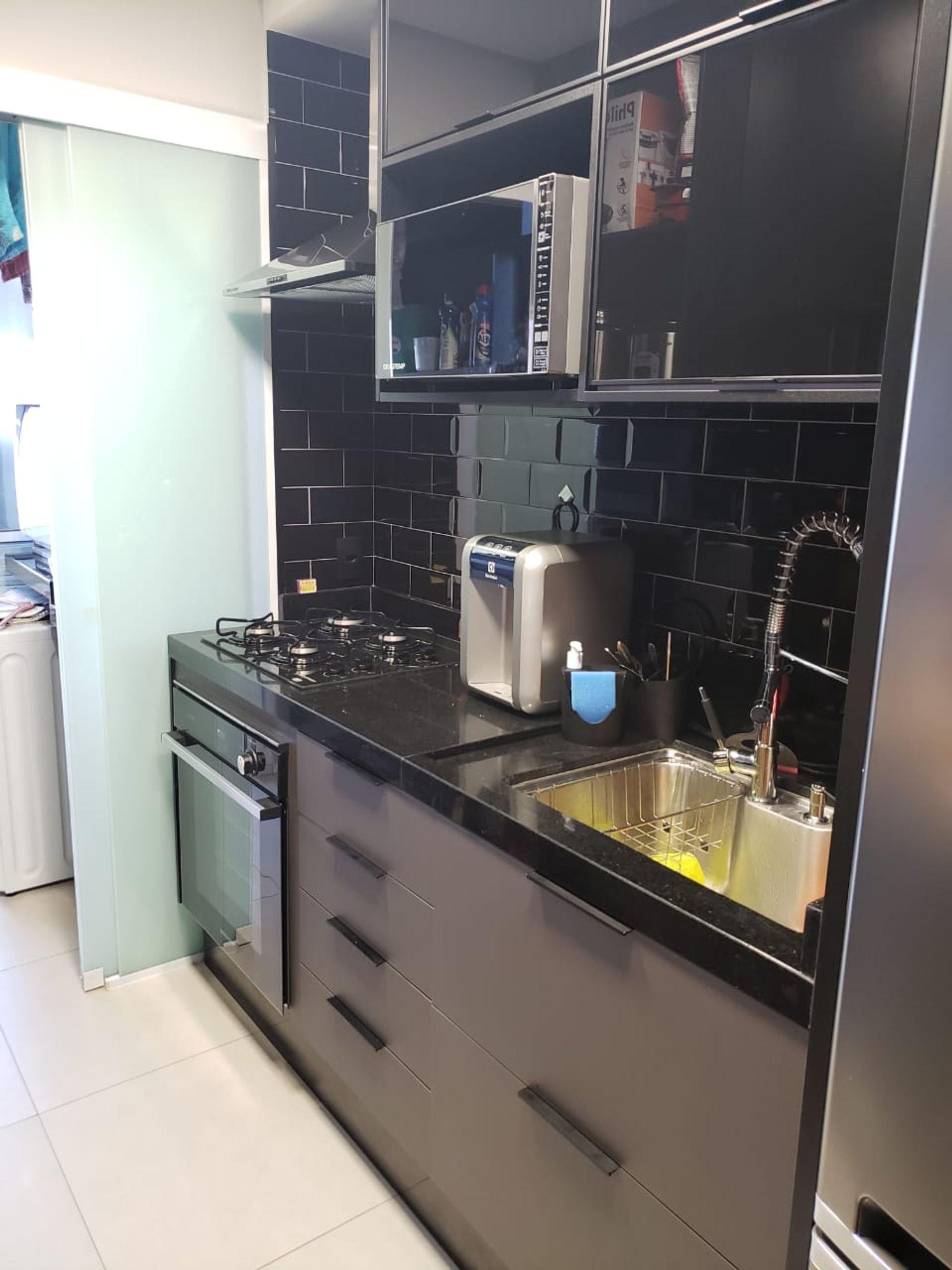 Foto de Cozinha com garrafa, forno, pia, microondas, xícara
