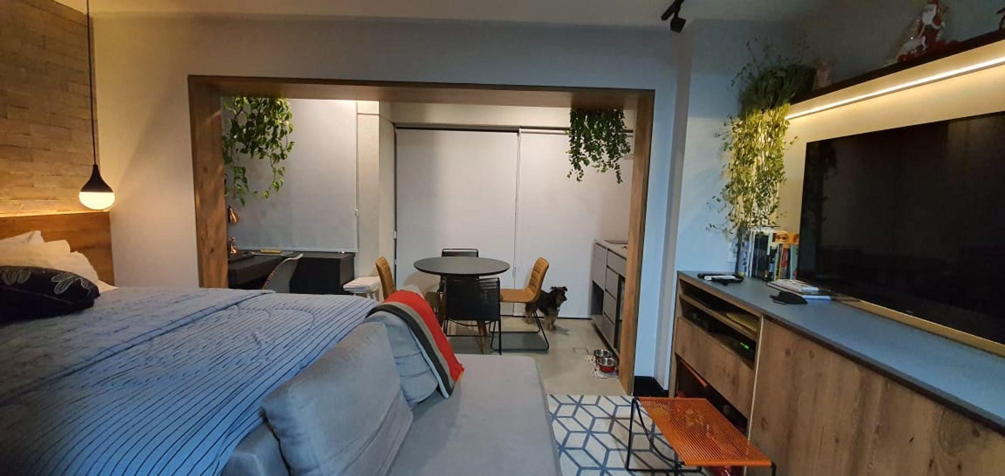 Foto de Quarto com cama, vaso de planta, televisão, cadeira