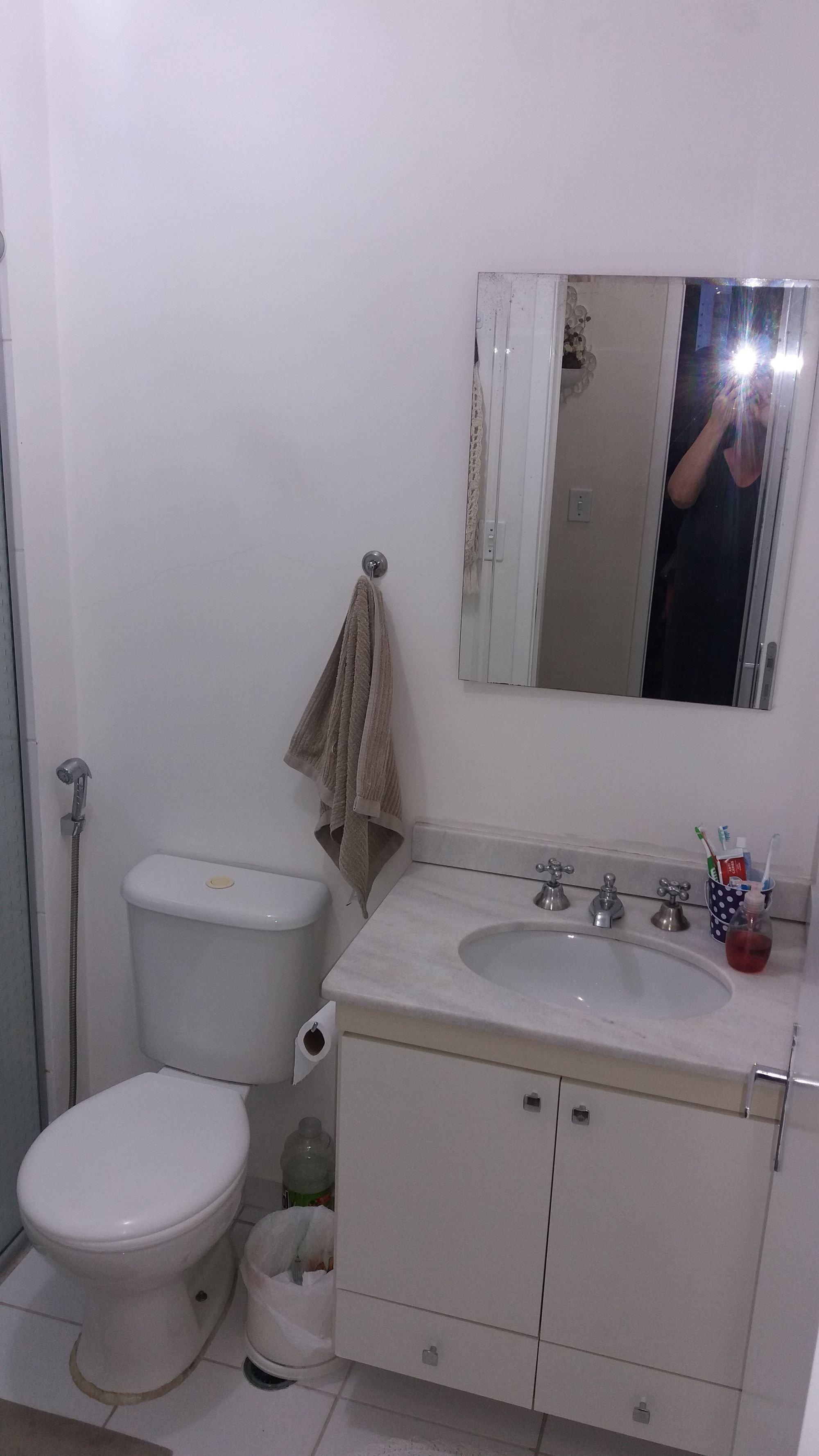Foto de Banheiro com escova de dente, vaso sanitário, pia, xícara
