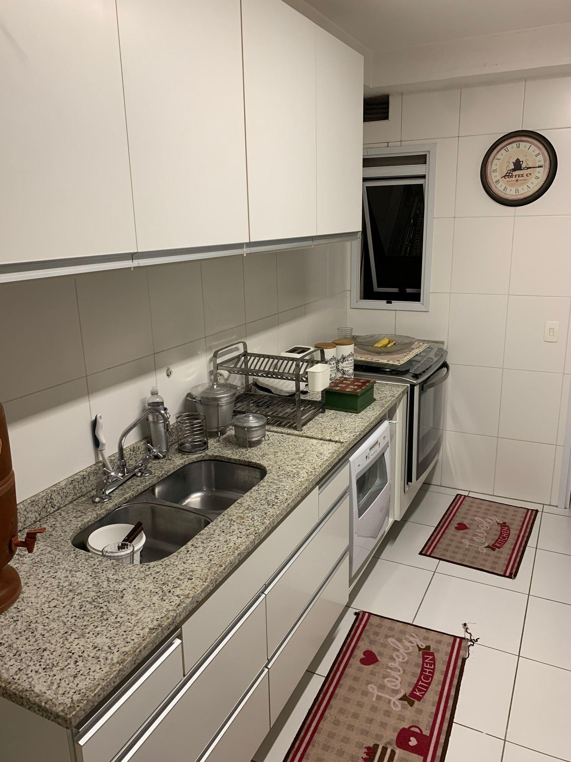 Foto de Cozinha com garrafa, relógio, tigela, pia
