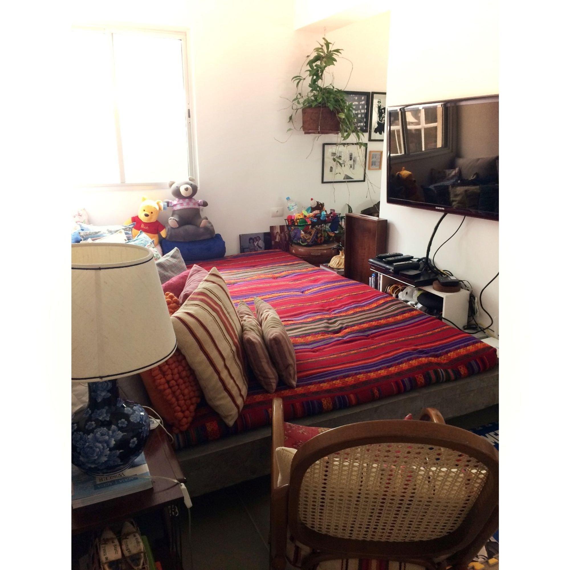 Foto de Quarto com cama, vaso de planta, cadeira