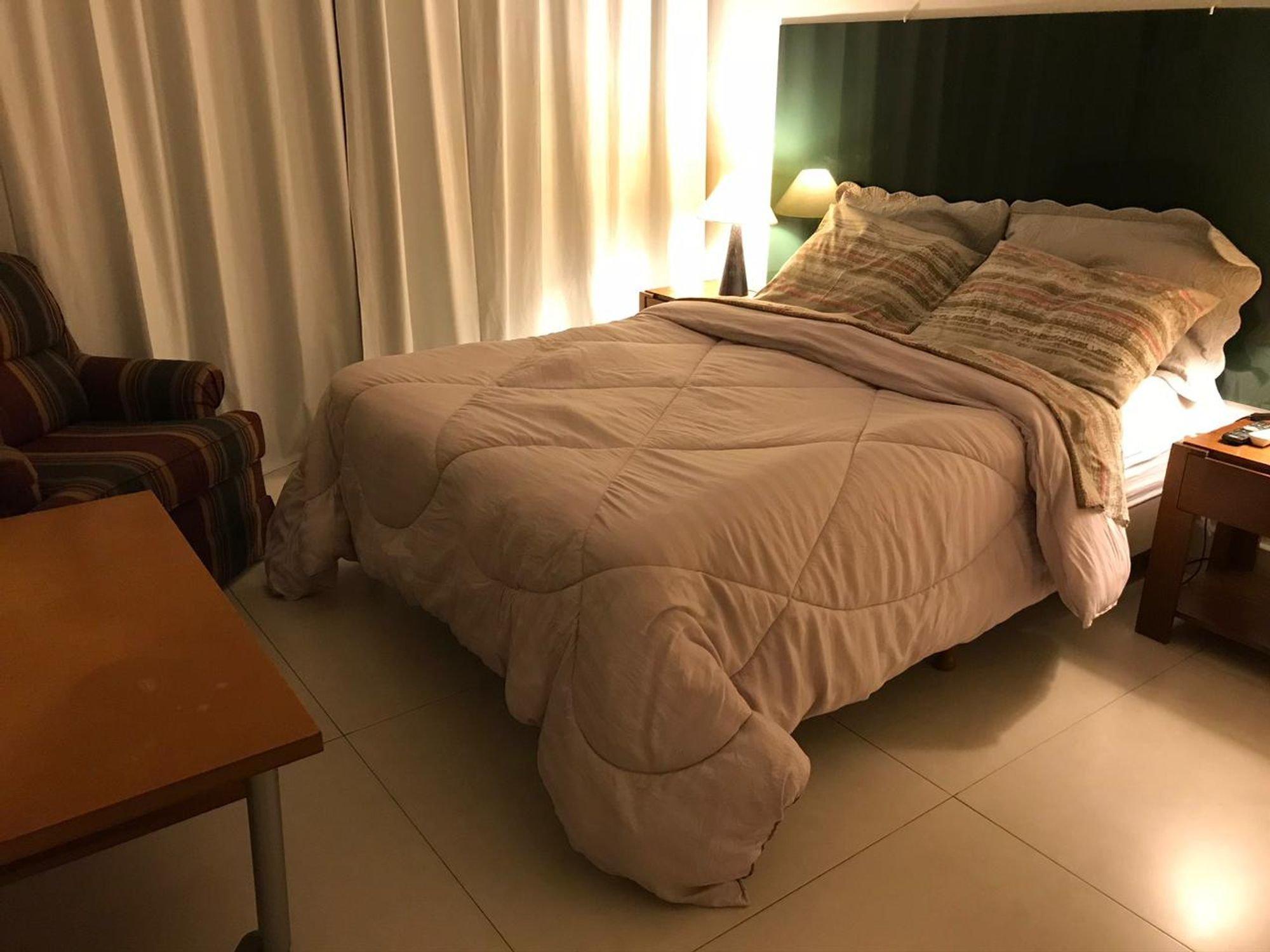 Foto de Quarto com cama, cadeira, mesa de jantar