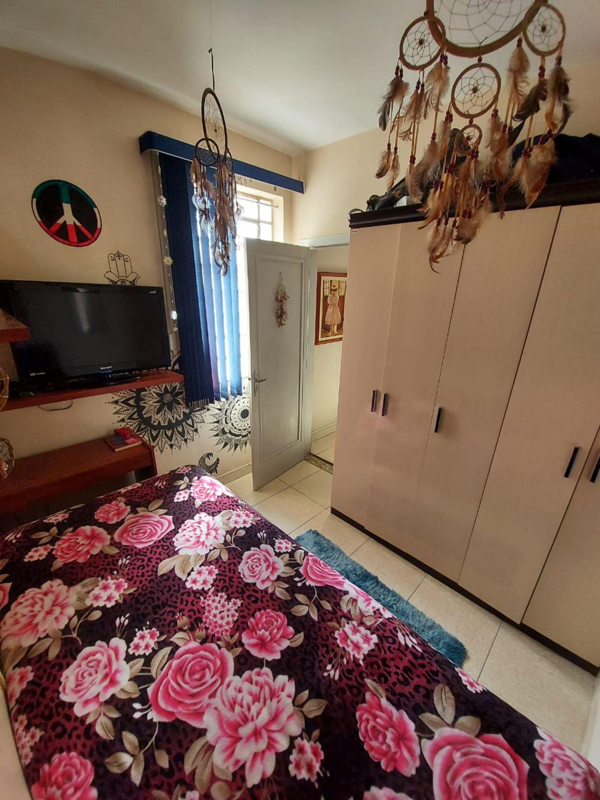 Foto de Quarto com cama, televisão, relógio