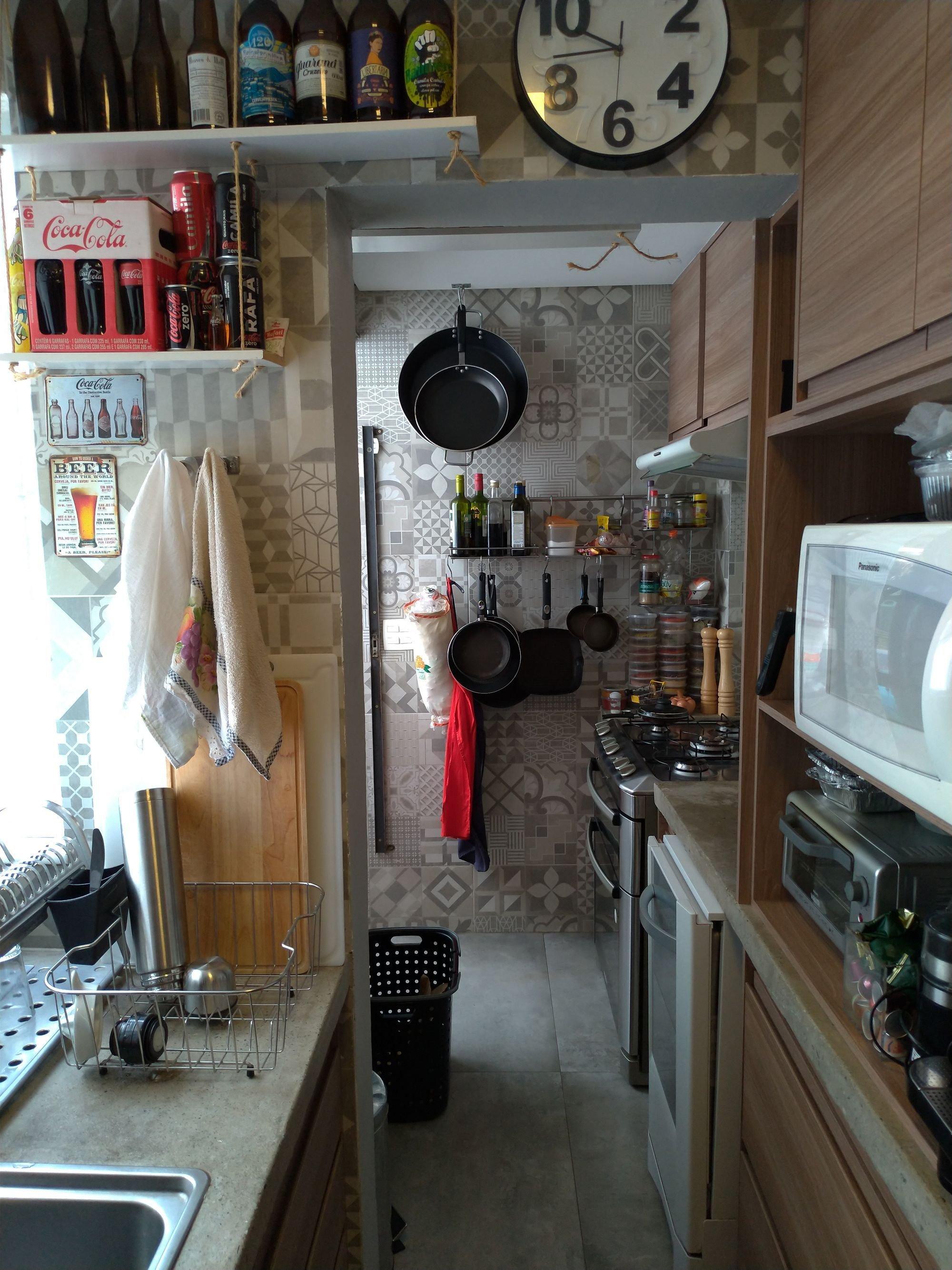 Foto de Cozinha com garrafa, relógio, forno, pia, microondas