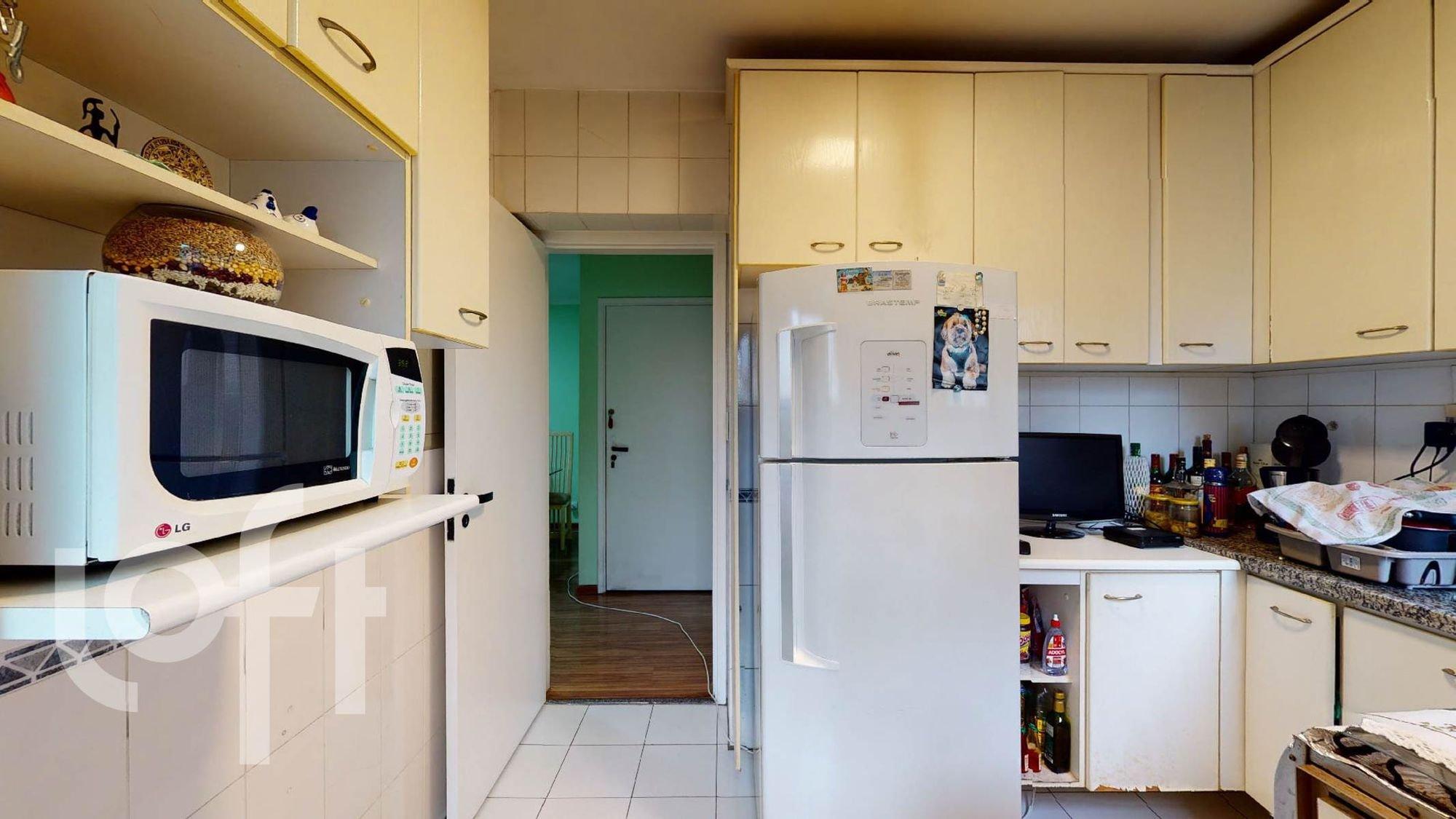 Foto de Cozinha com televisão, garrafa, geladeira, microondas