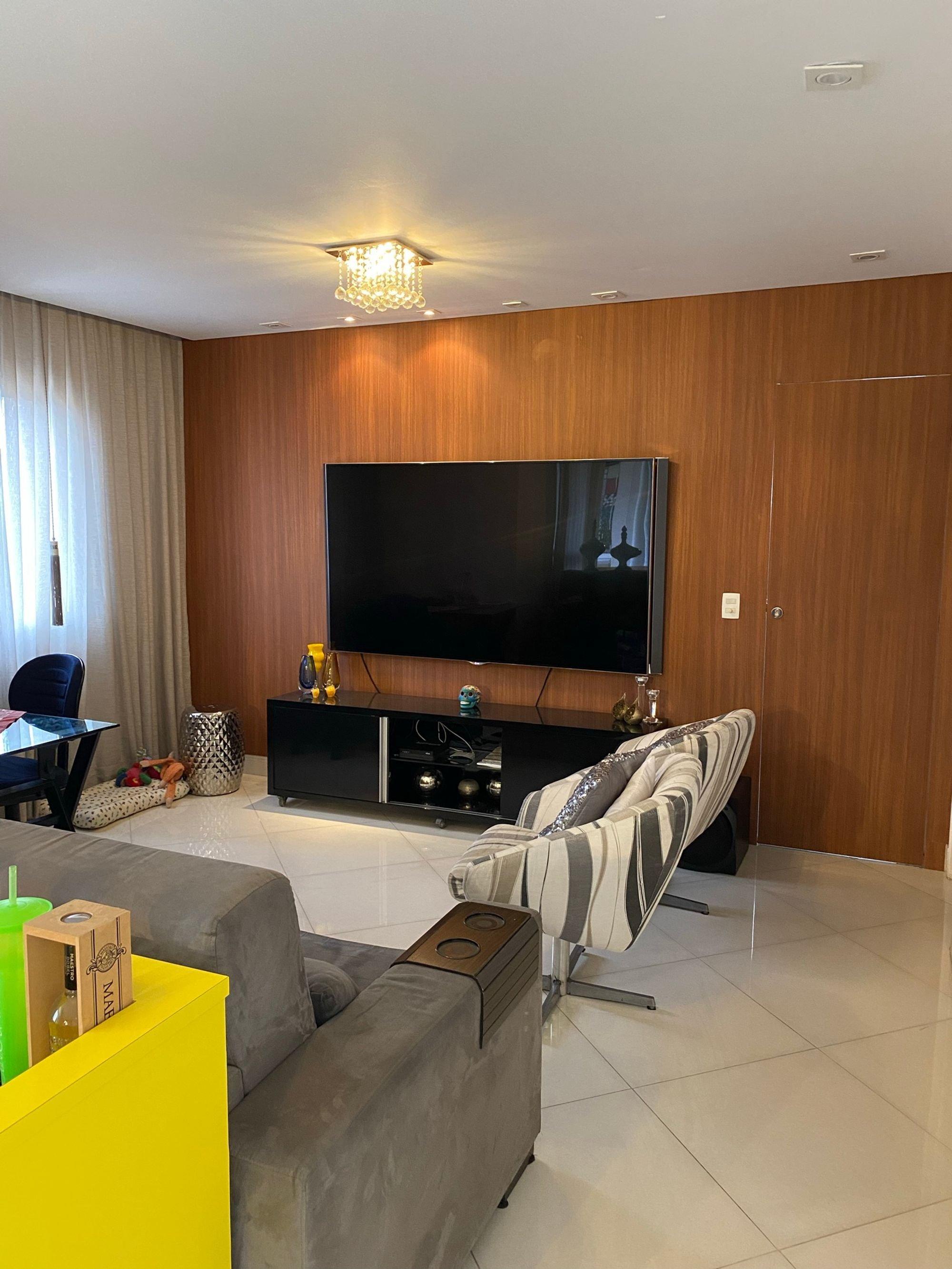 Foto de Sala com sofá, televisão, garrafa, cadeira