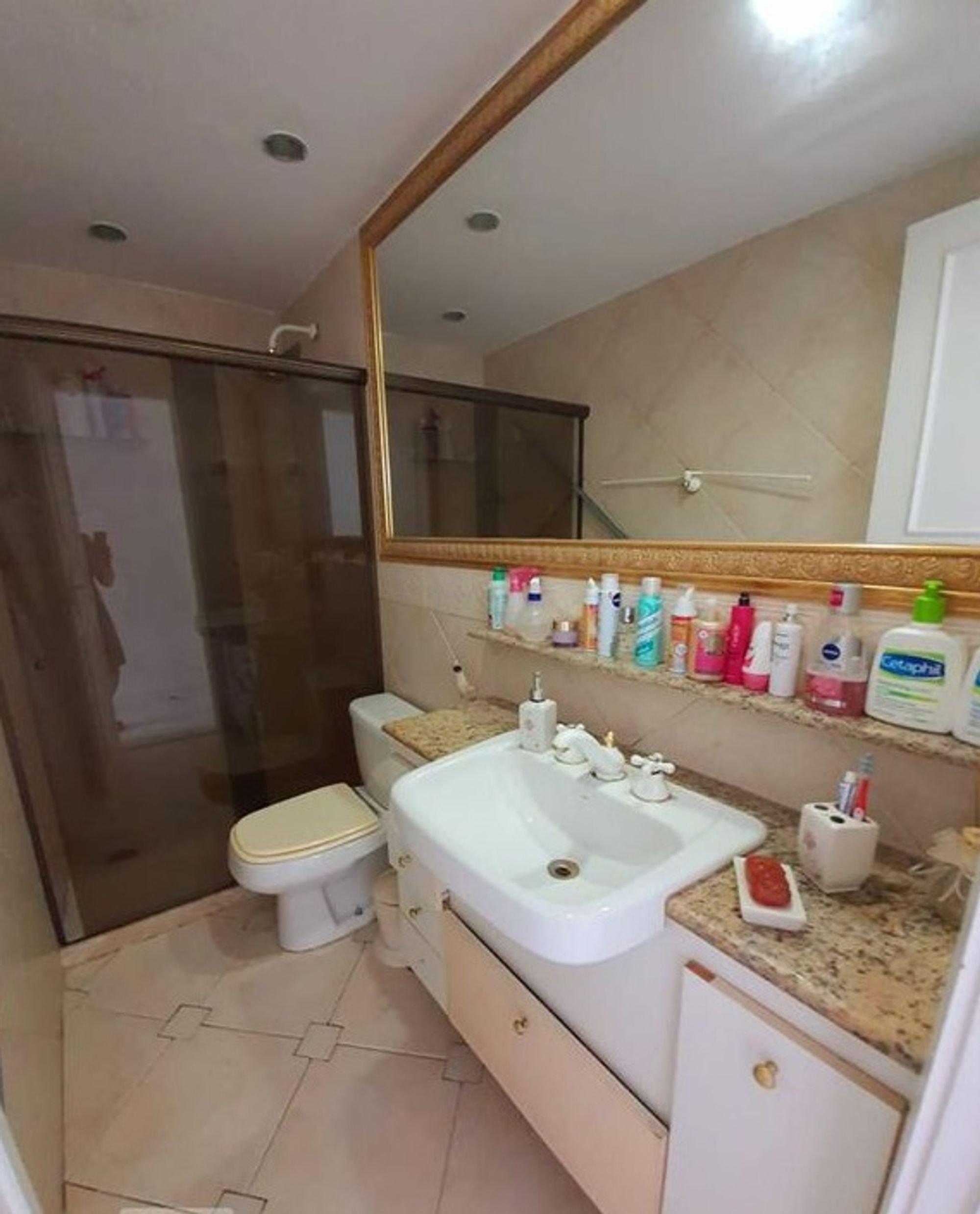 Foto de Banheiro com escova de dente, vaso sanitário, garrafa, pia, xícara
