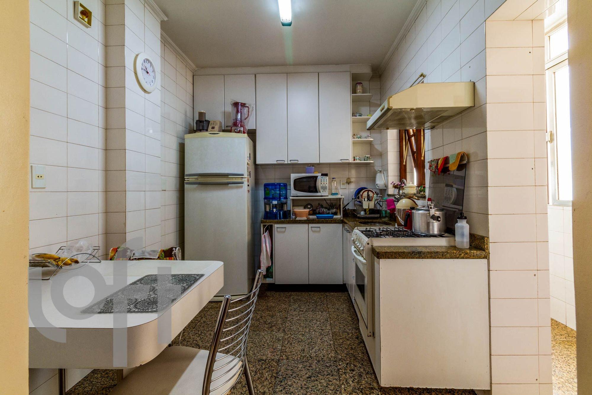 Foto de Cozinha com forno, cadeira, pia, relógio, garrafa, tigela, geladeira, microondas