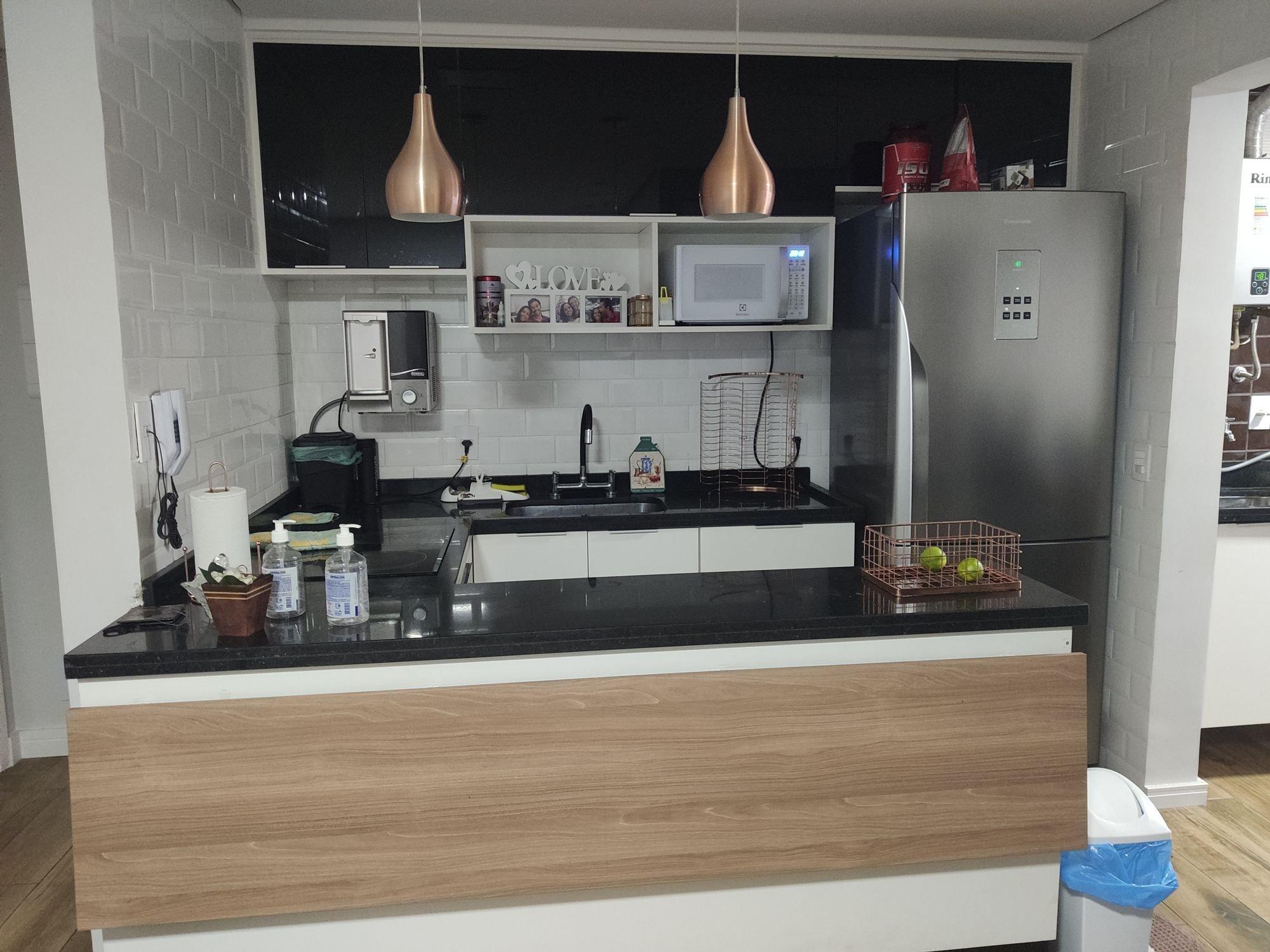 Foto de Cozinha com vaso, garrafa, geladeira, microondas