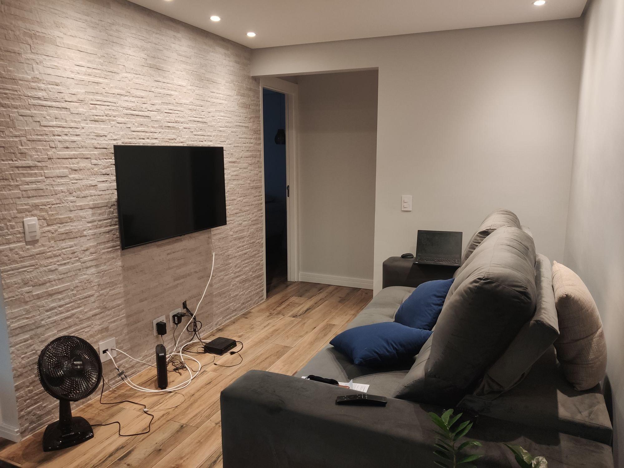 Foto de Sala com computador portátil, controle remoto, sofá