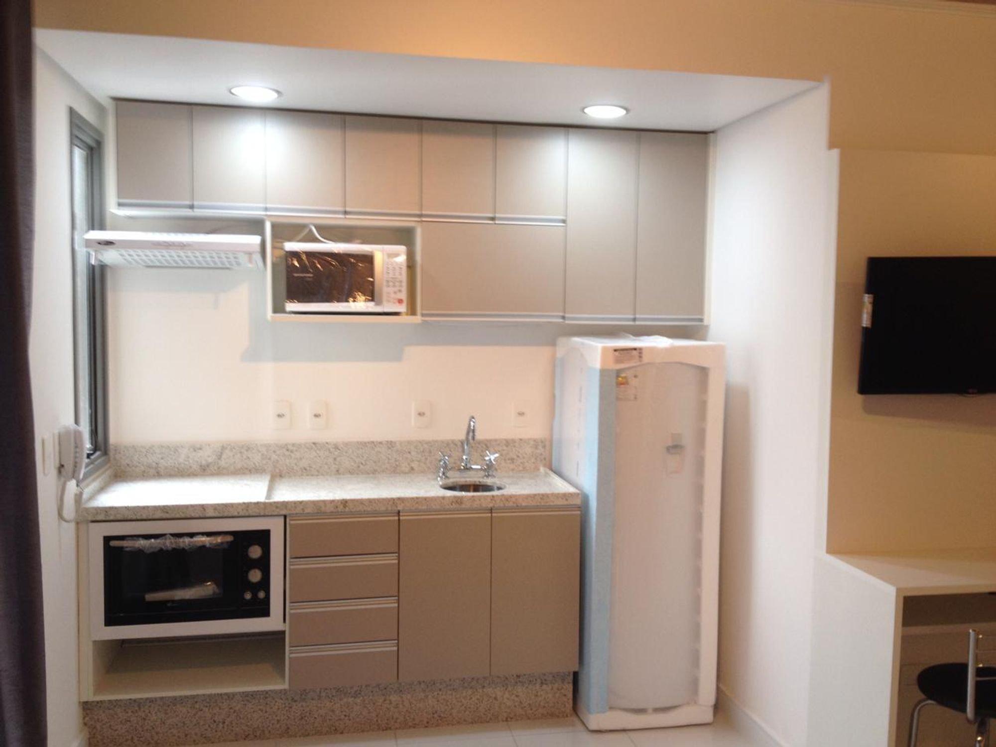 Foto de Cozinha com televisão, geladeira, pia, microondas