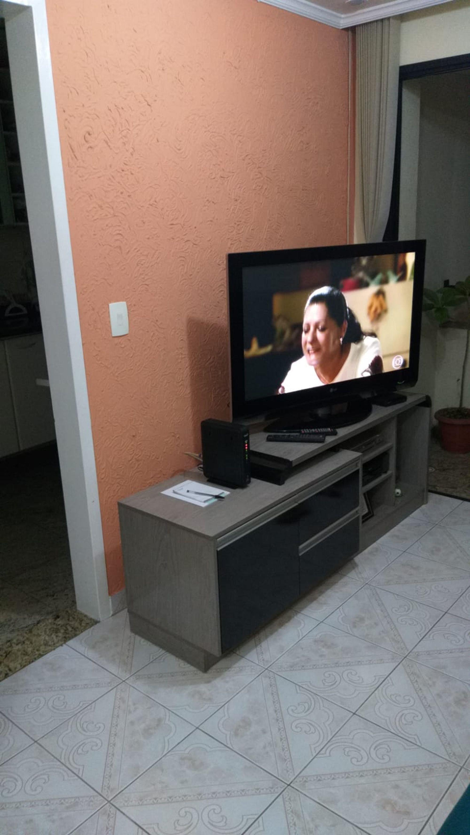 Foto de Sala com vaso de planta, televisão, pessoa