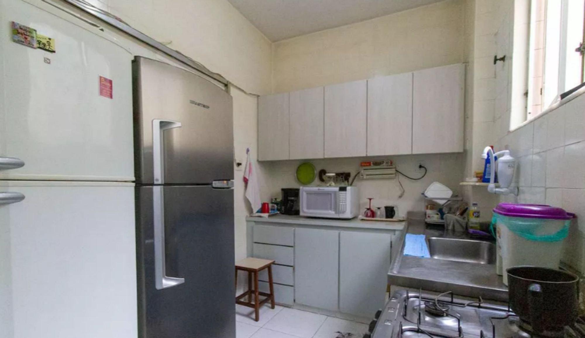 Foto de Cozinha com forno, pia, cadeira, garrafa, geladeira, microondas, xícara