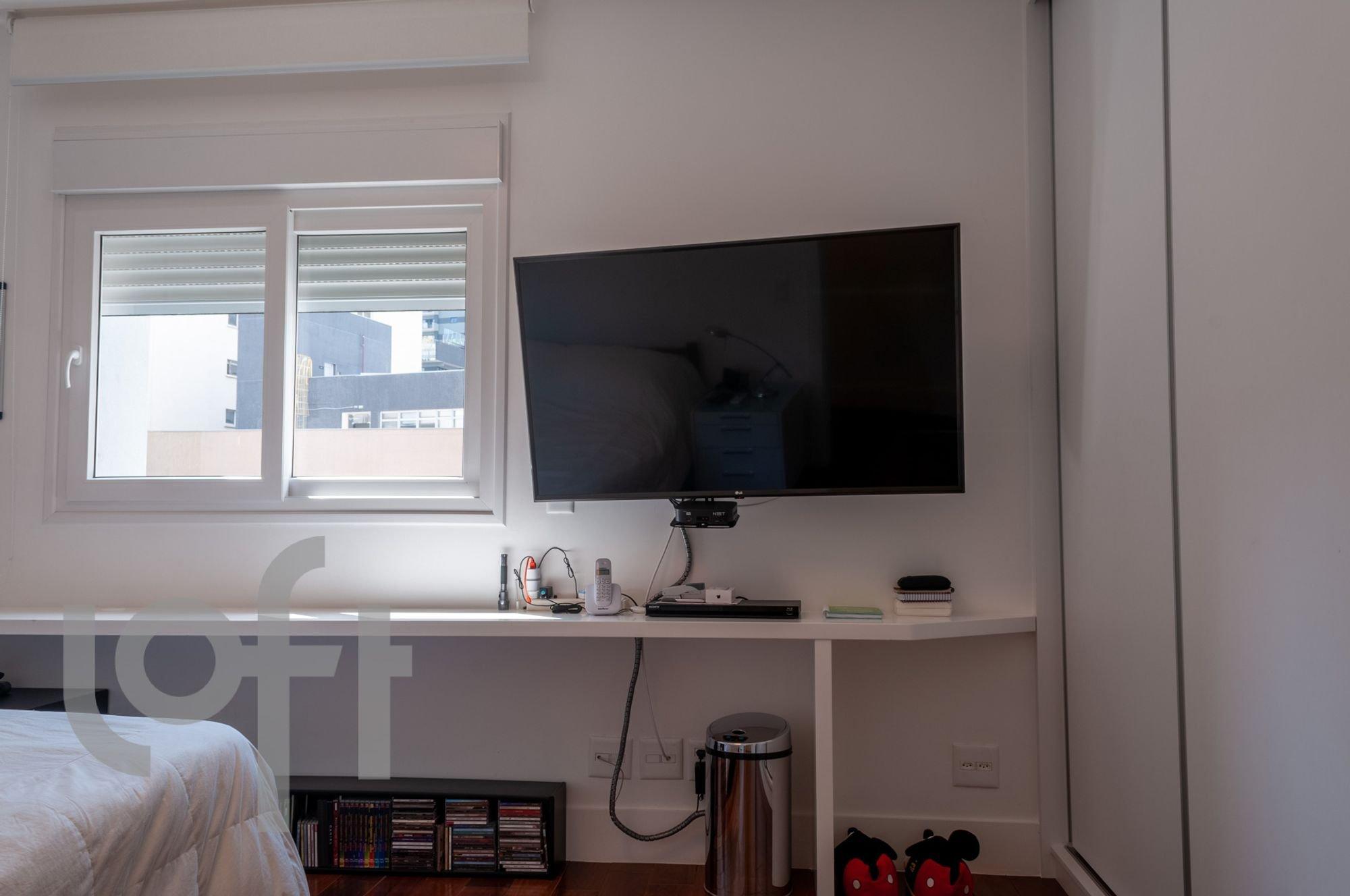 Foto de Quarto com cama, televisão, livro