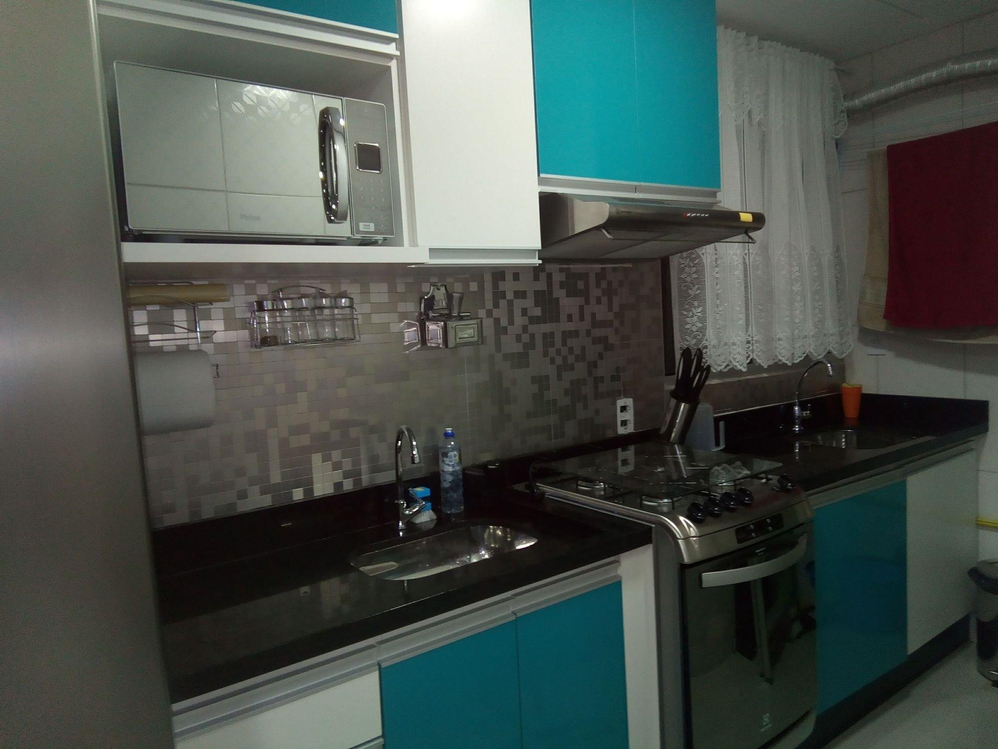 Foto de Cozinha com faca, garrafa, forno, pia, microondas, xícara