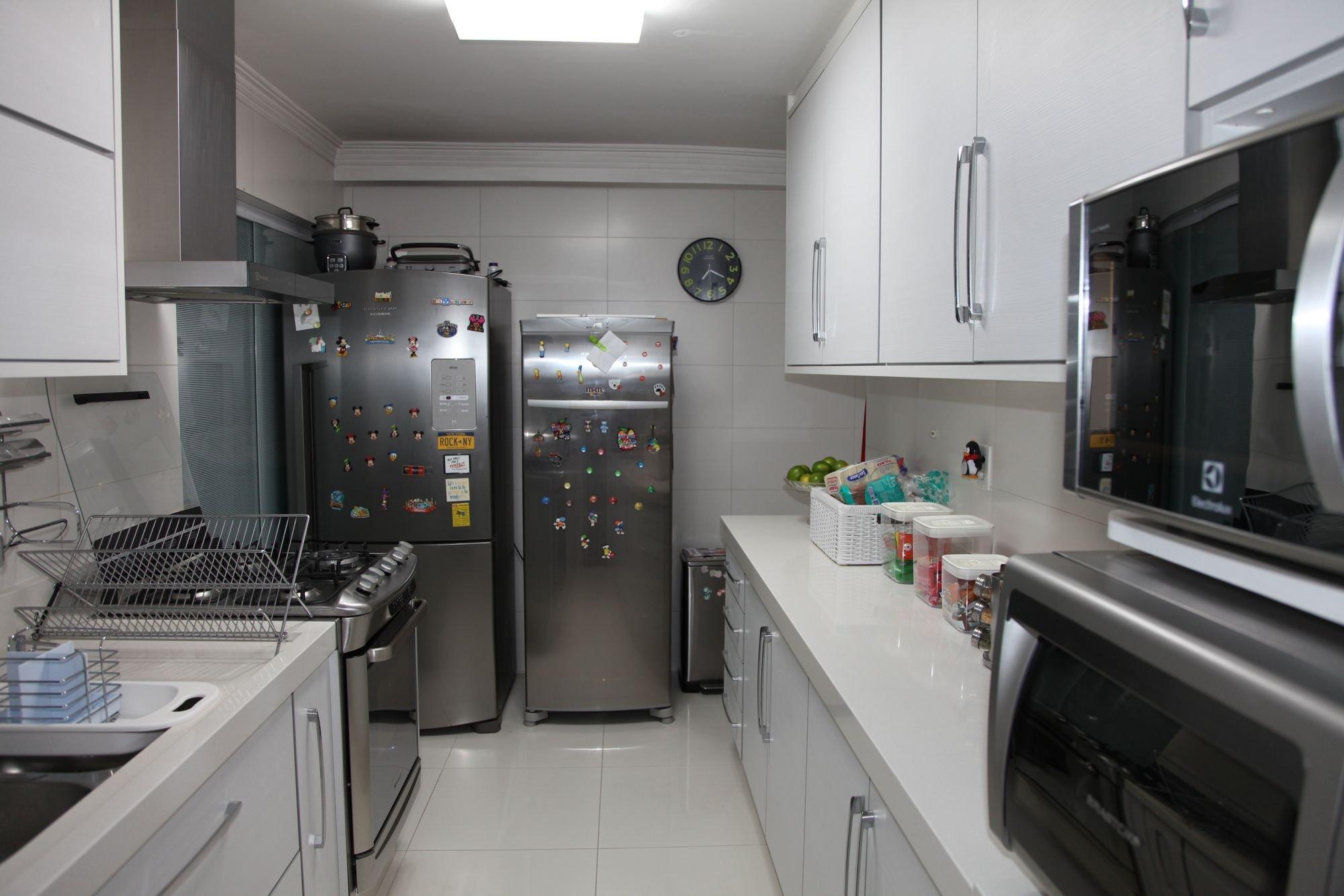 Foto de Cozinha com relógio, forno, geladeira, microondas, xícara