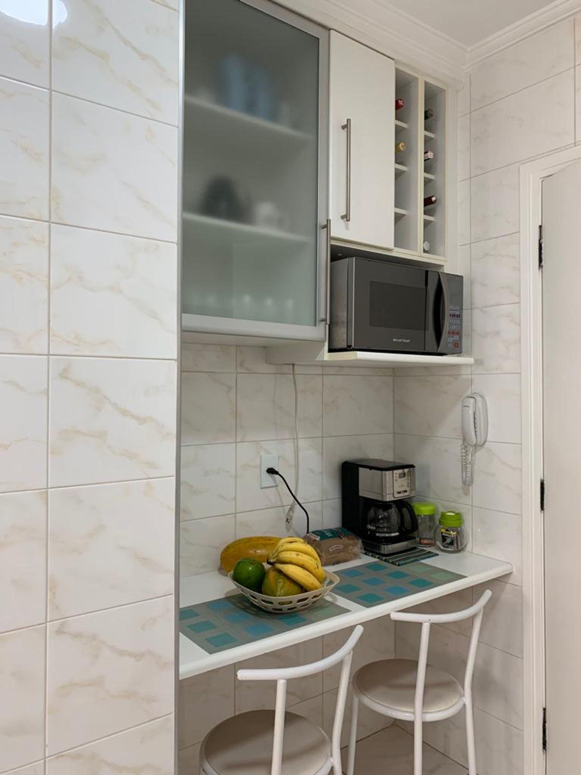 Foto de Cozinha com tigela, cadeira, microondas, xícara