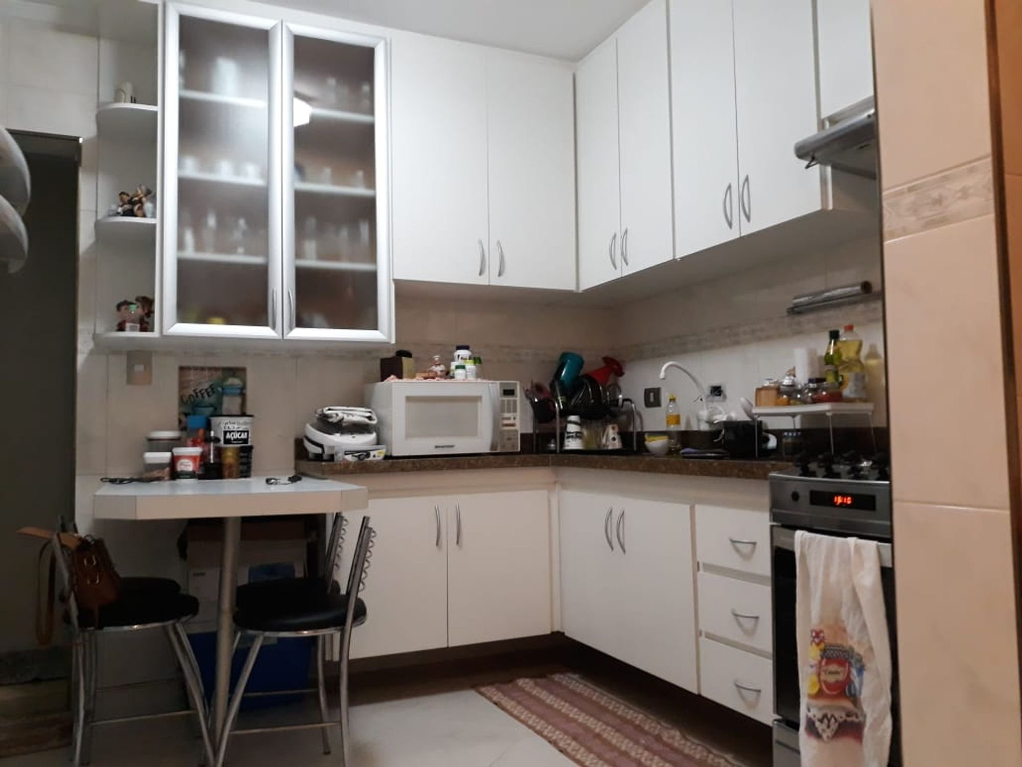 Foto de Cozinha com garrafa, forno, cadeira, microondas, xícara