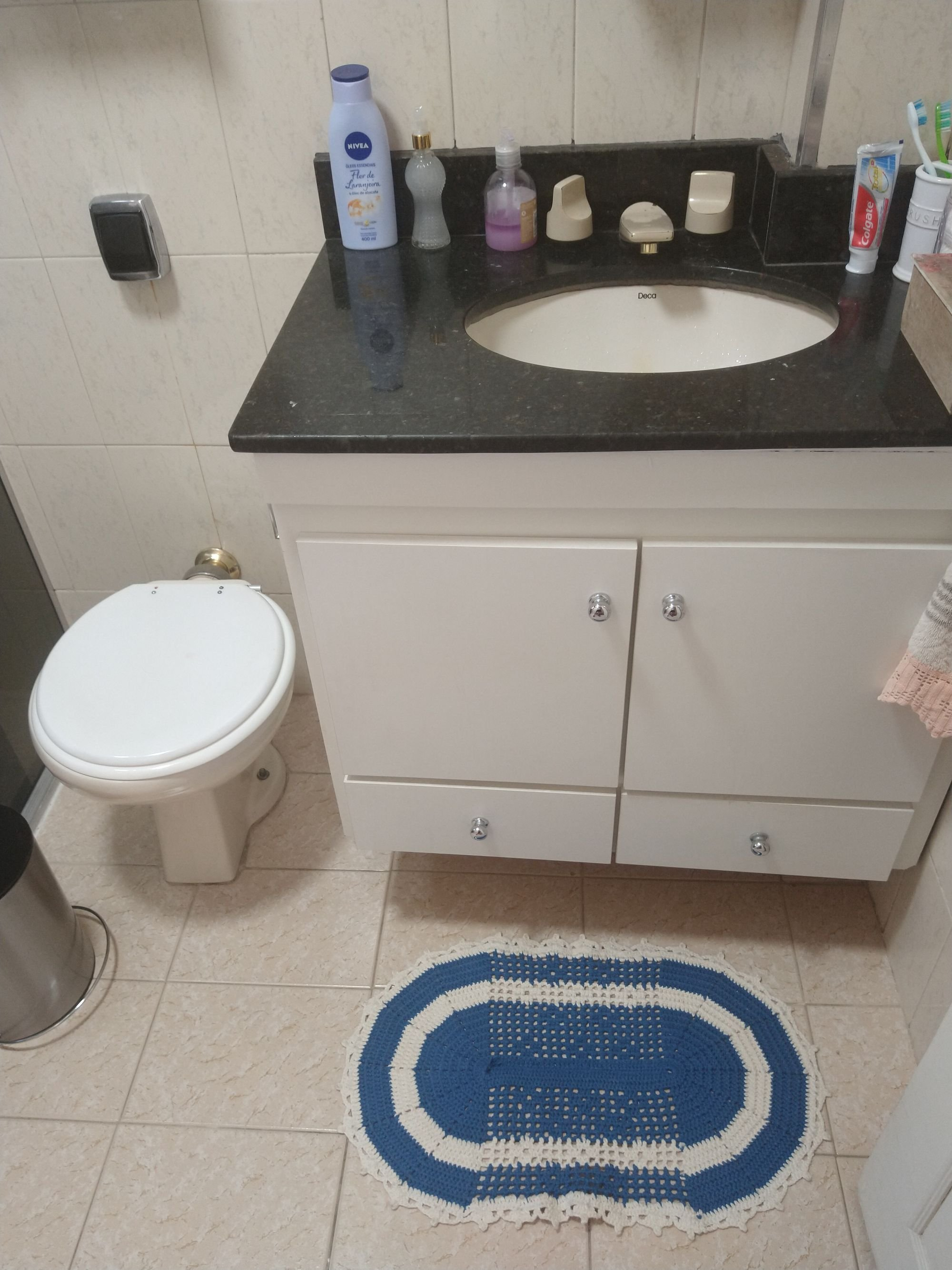 Foto de Banheiro com escova de dente, vaso sanitário, garrafa, pia