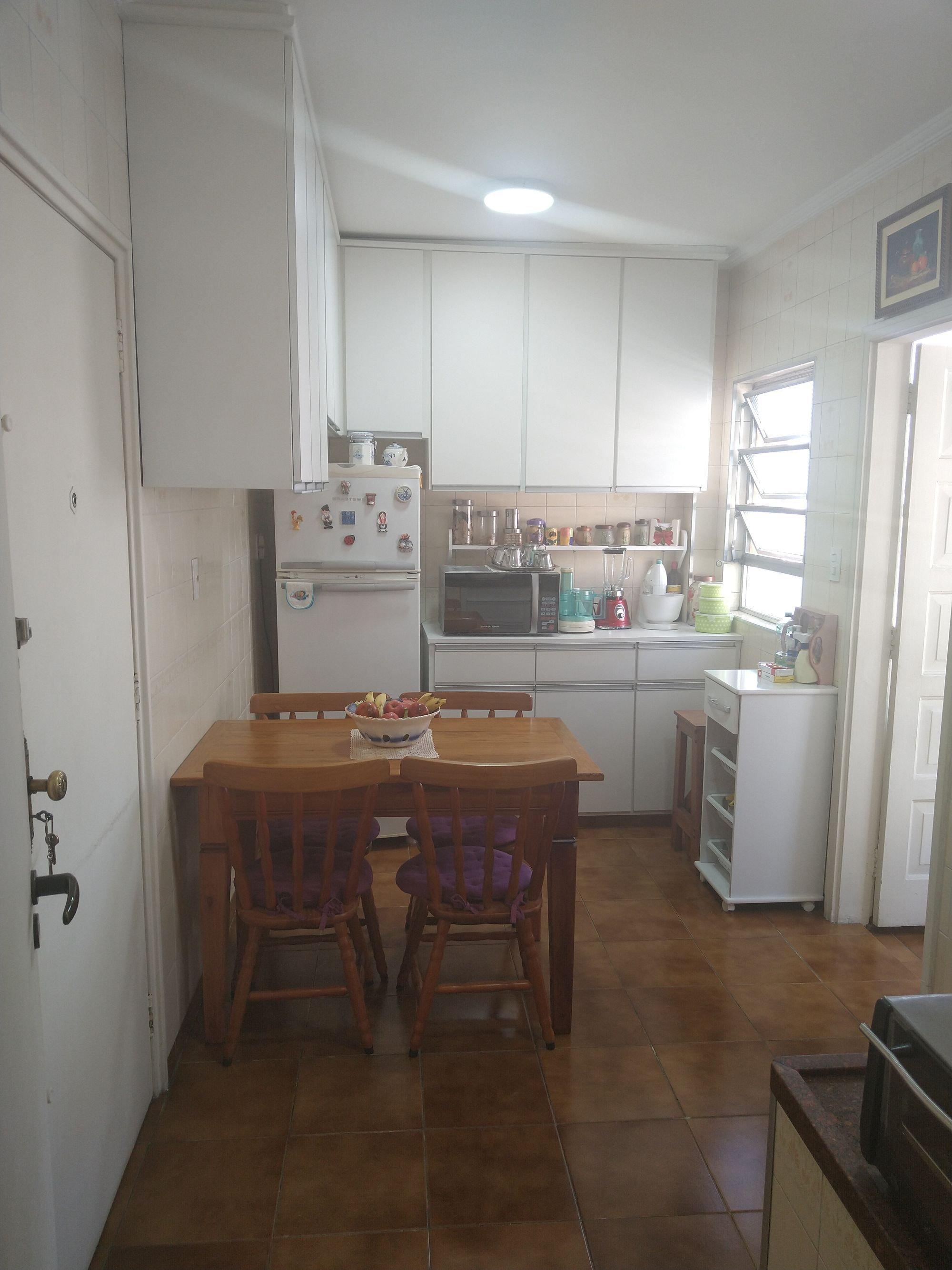 Foto de Cozinha com garrafa, tigela, geladeira, cadeira, microondas, mesa de jantar
