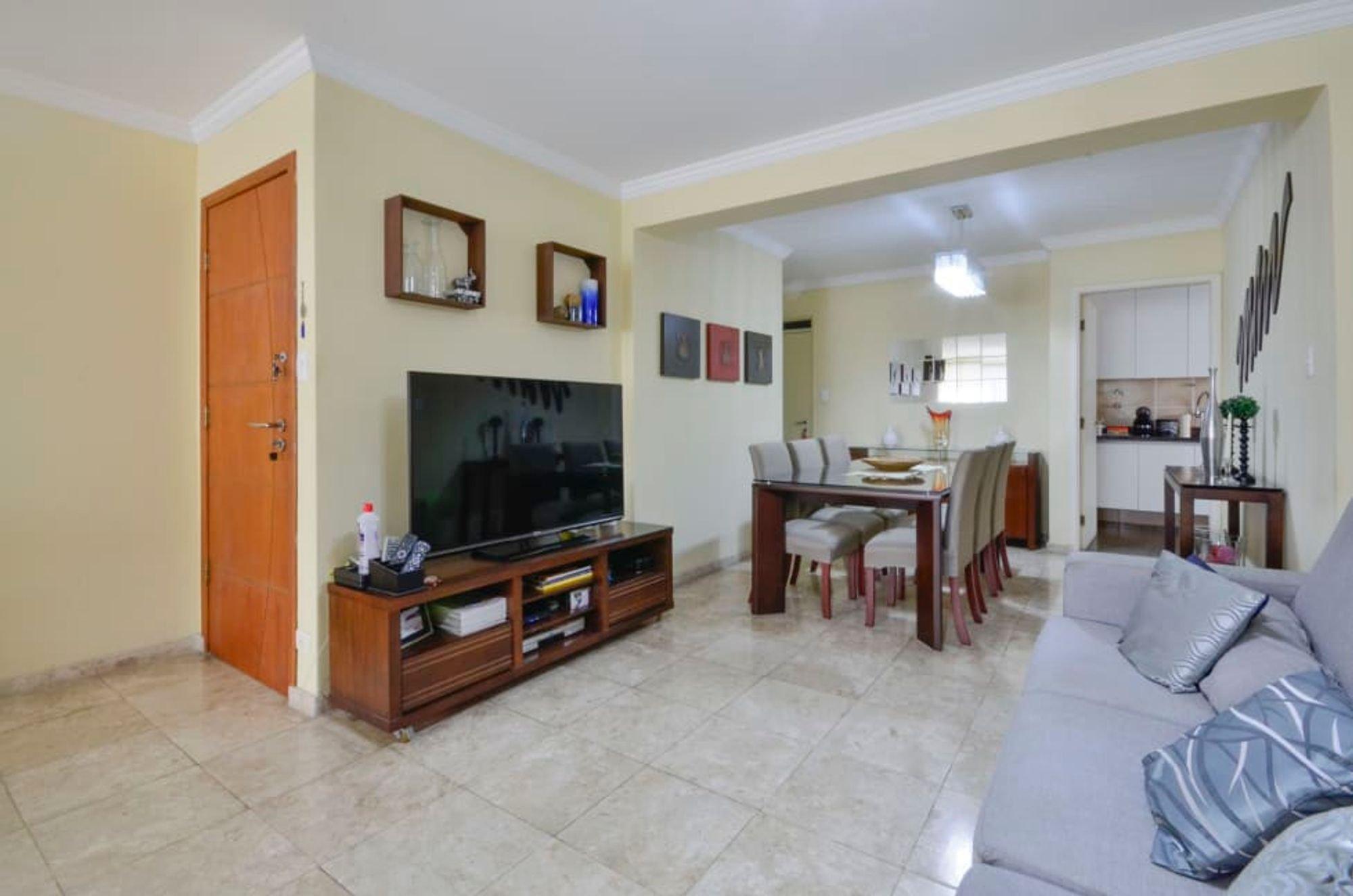Foto de Sala com sofá, televisão, vaso, tigela, cadeira, mesa de jantar