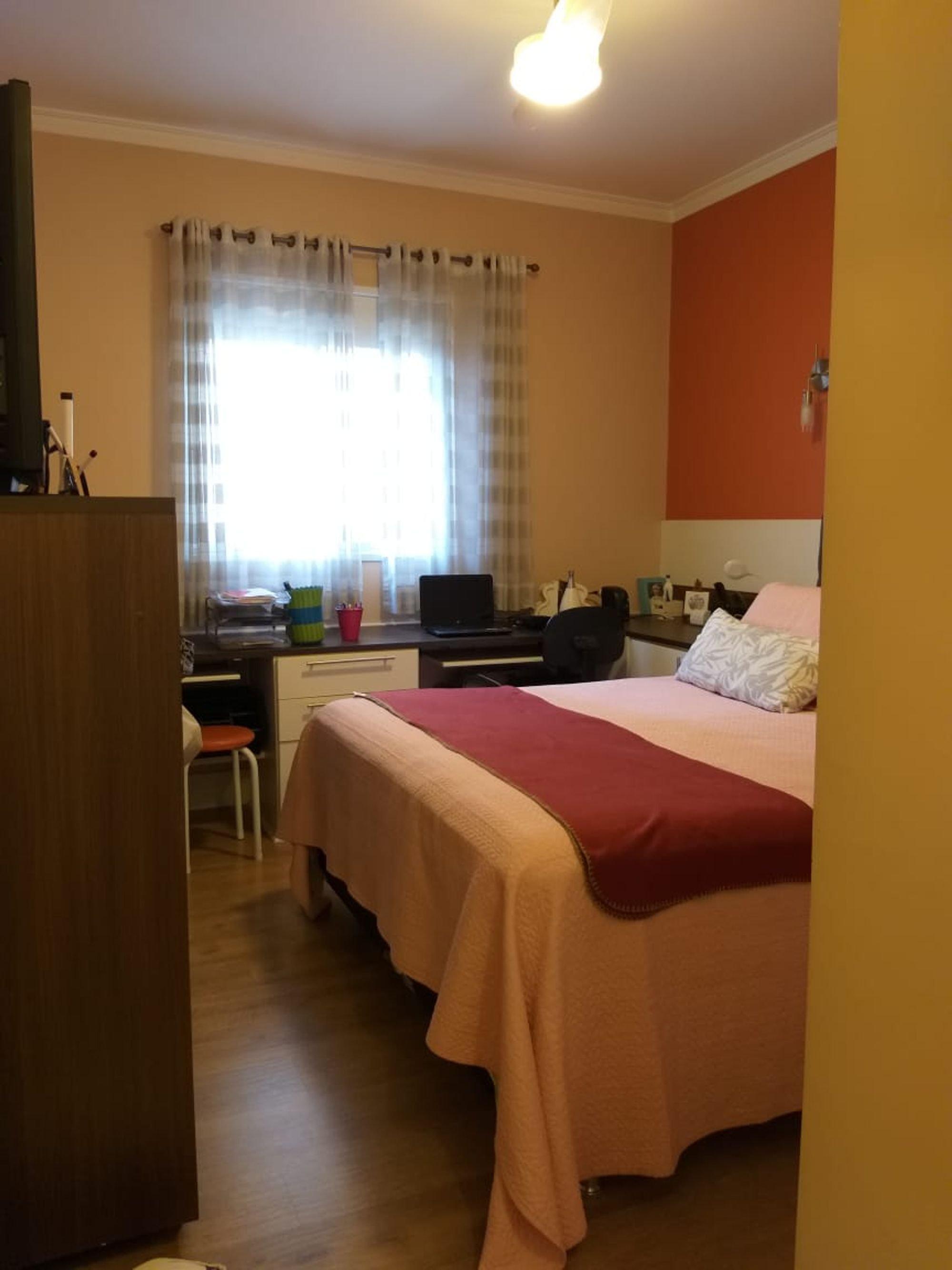Foto de Quarto com cama, televisão, cadeira, xícara