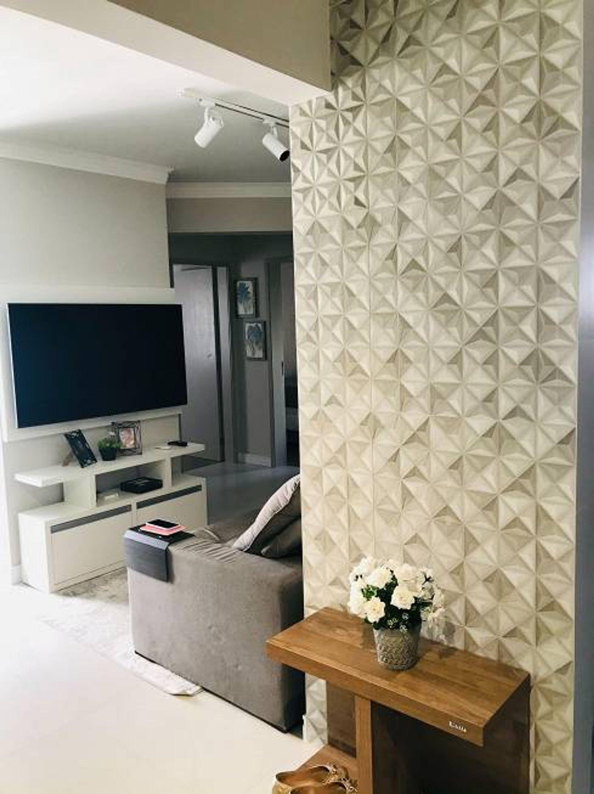 Foto de Sala com vaso de planta, sofá, televisão, vaso, livro