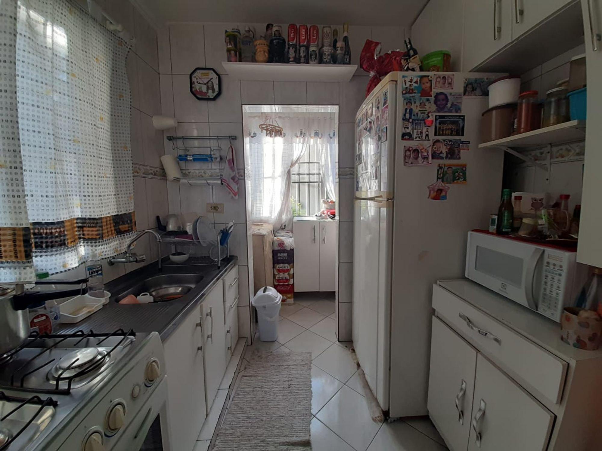 Foto de Cozinha com garrafa, relógio, forno, tigela, geladeira, microondas