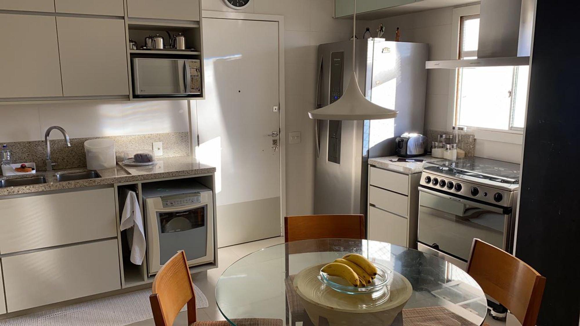 Foto de Cozinha com forno, tigela, geladeira, cadeira, microondas, mesa de jantar