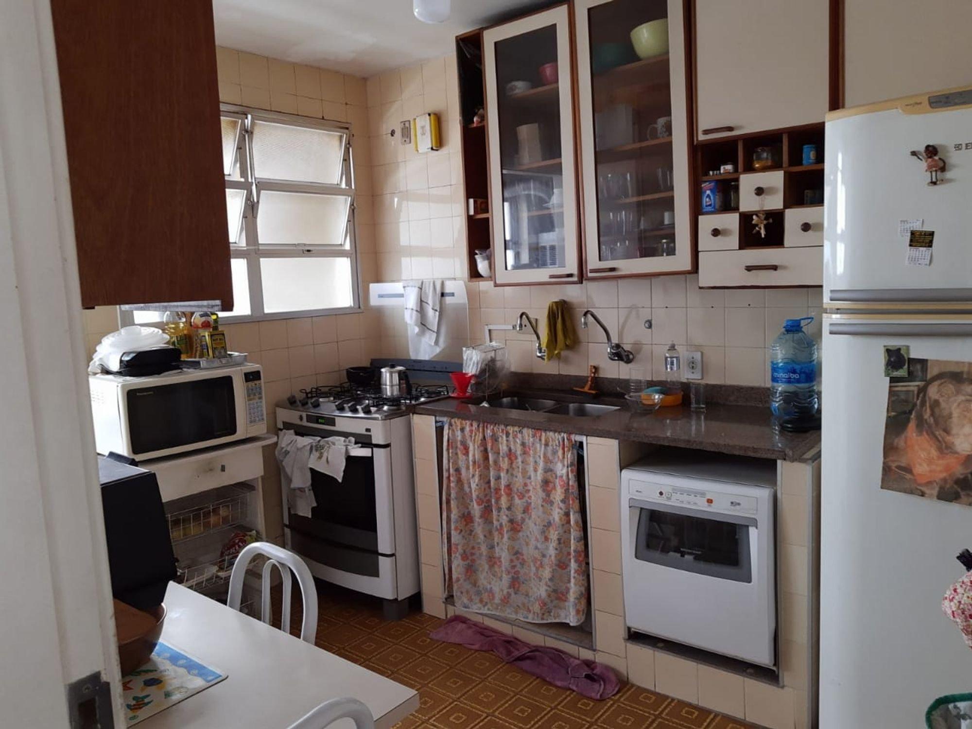 Foto de Cozinha com televisão, forno, pia, cadeira, mesa de jantar, garrafa, tigela, geladeira, microondas, xícara