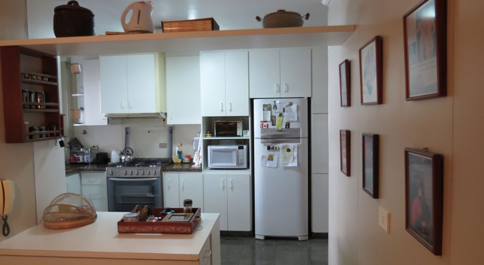 Foto de Cozinha com forno, geladeira, microondas, mesa de jantar, livro