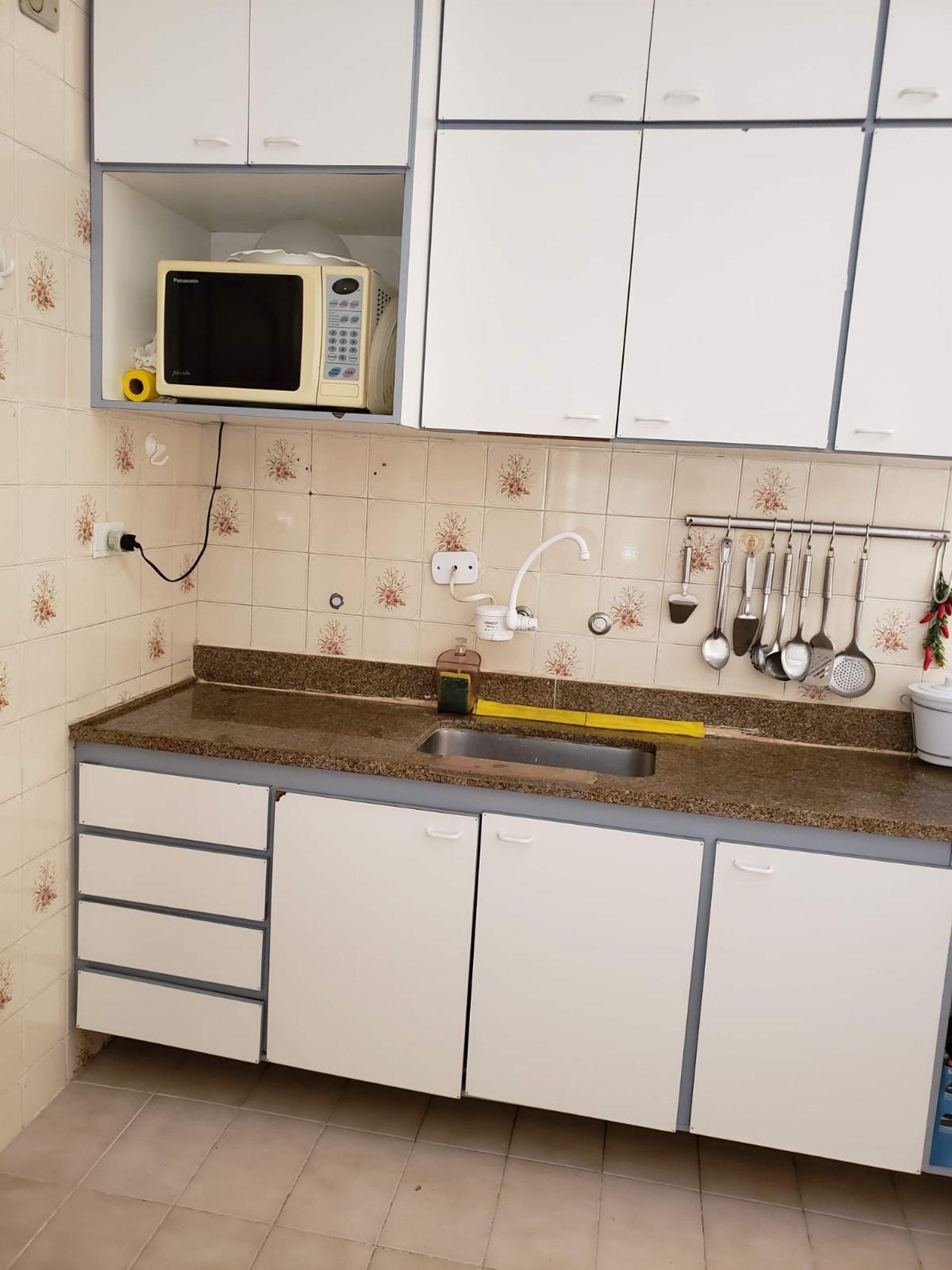 Foto de Cozinha com colher, microondas, garrafa