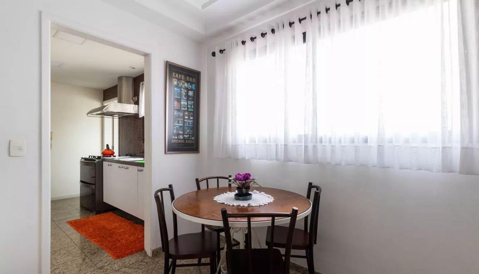 Foto de Sala com televisão, vaso, garrafa, forno, cadeira, mesa de jantar