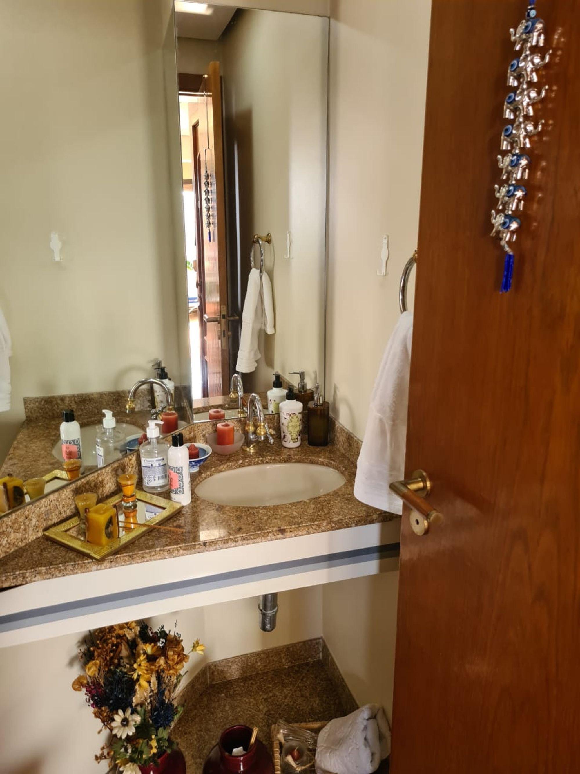 Foto de Banheiro com vaso de planta, garrafa, pia, xícara