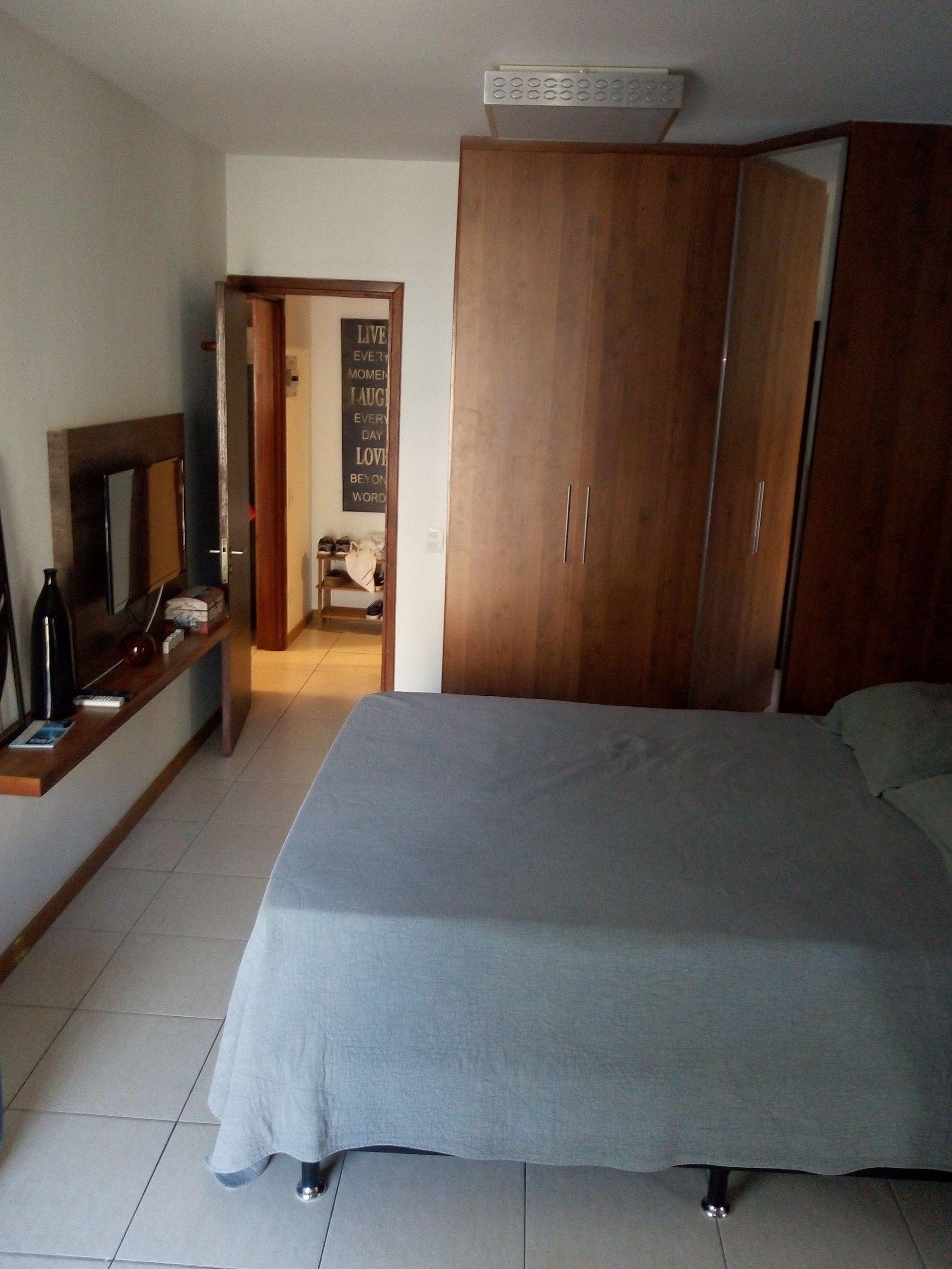 Foto de Quarto com cama, televisão, garrafa