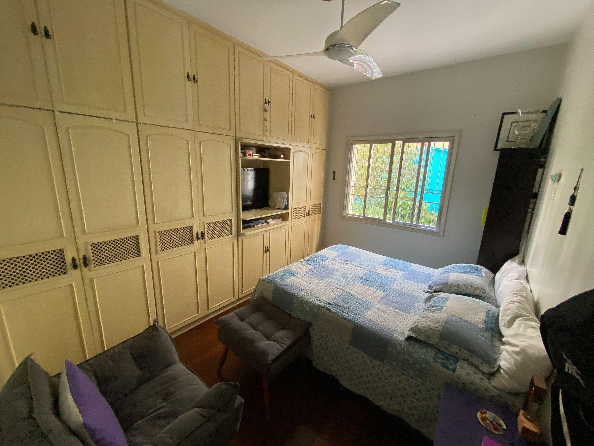 Foto de Quarto com cama, sofá, televisão, cadeira