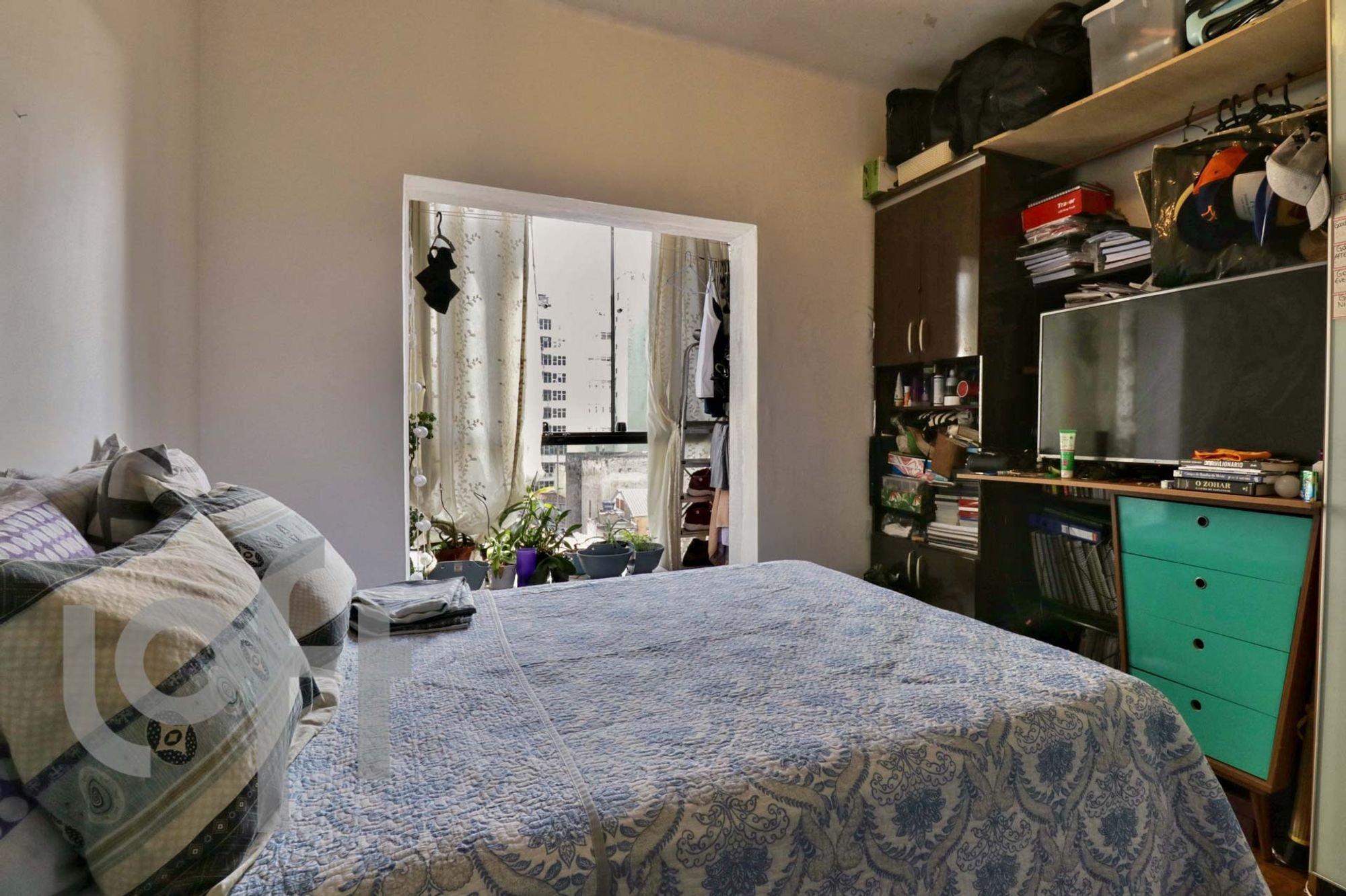 Foto de Quarto com vaso de planta, cama, televisão, livro