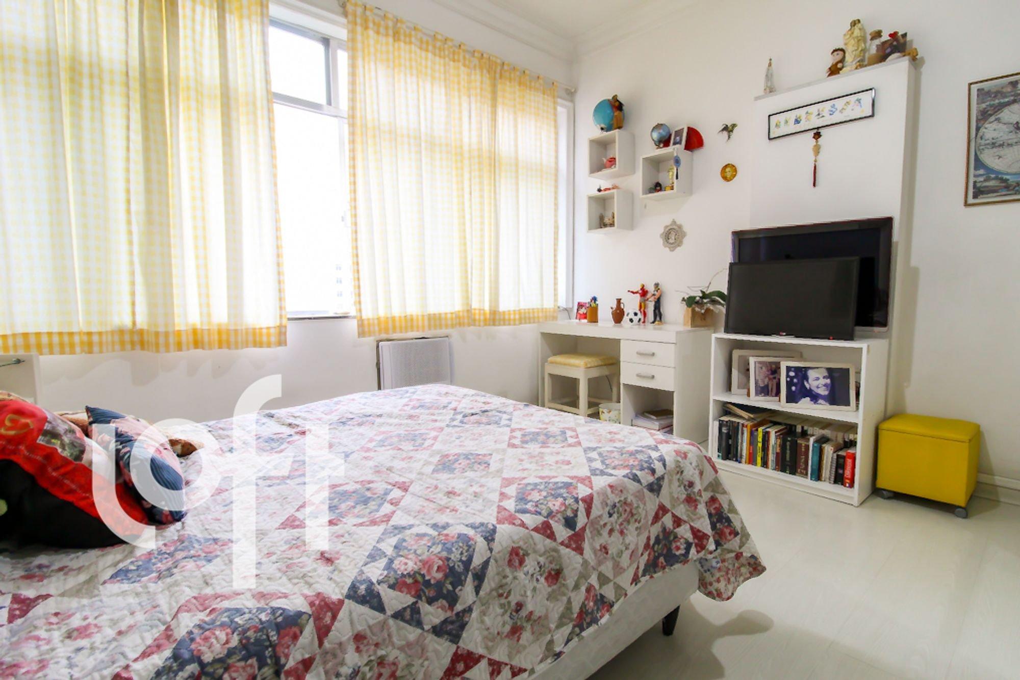 Foto de Quarto com cama, vaso de planta, televisão, livro