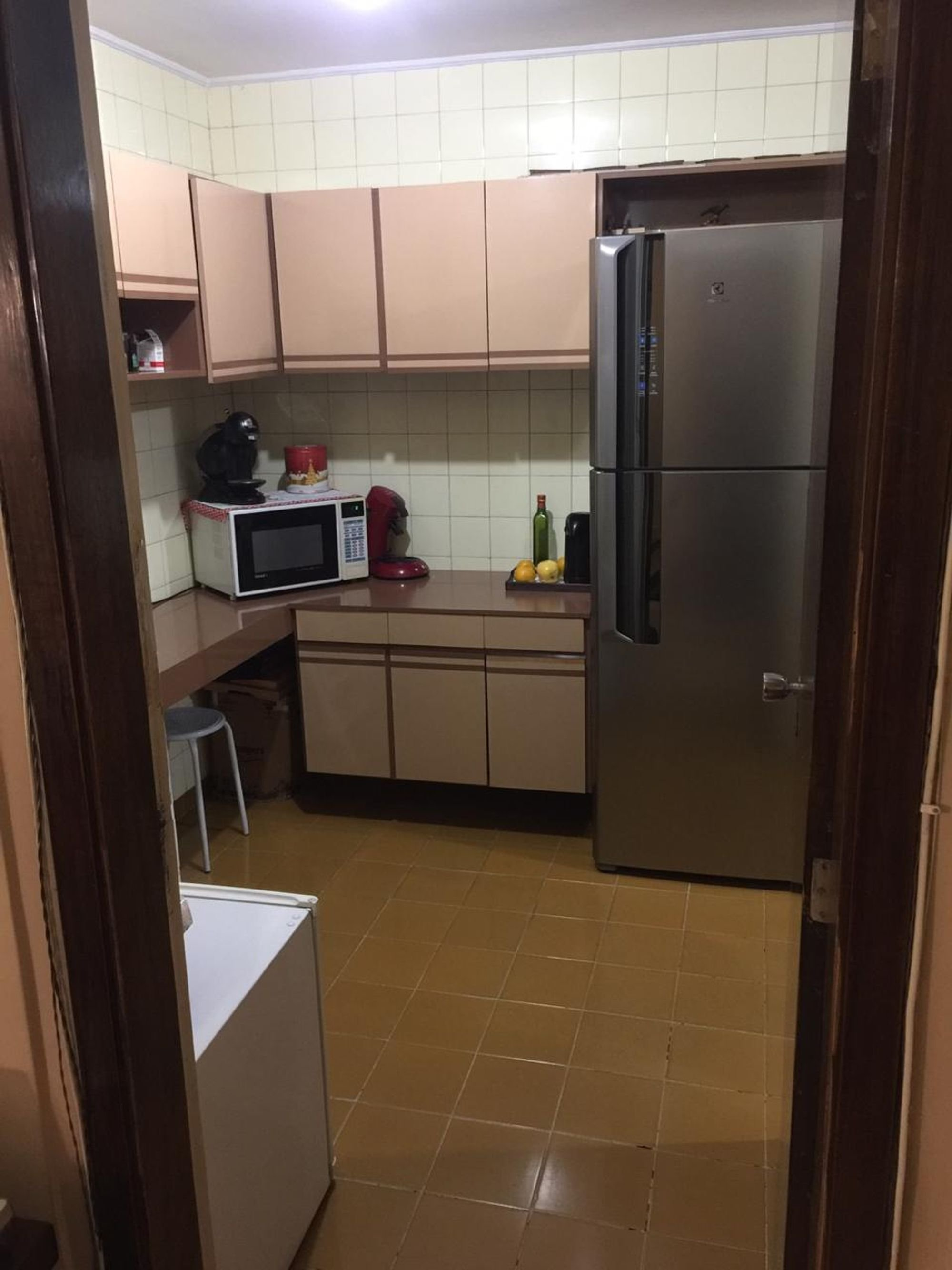 Foto de Cozinha com garrafa, geladeira, cadeira, microondas
