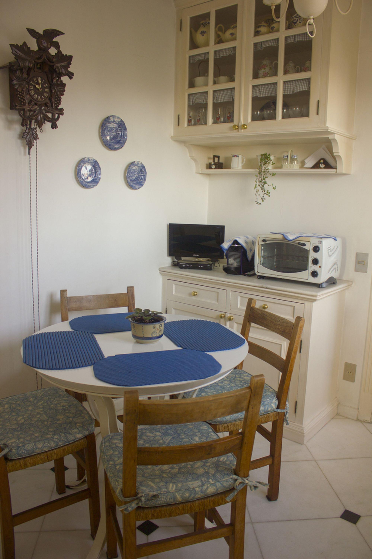 Foto de Sala com vaso de planta, televisão, cadeira, mesa de jantar, relógio, microondas, xícara