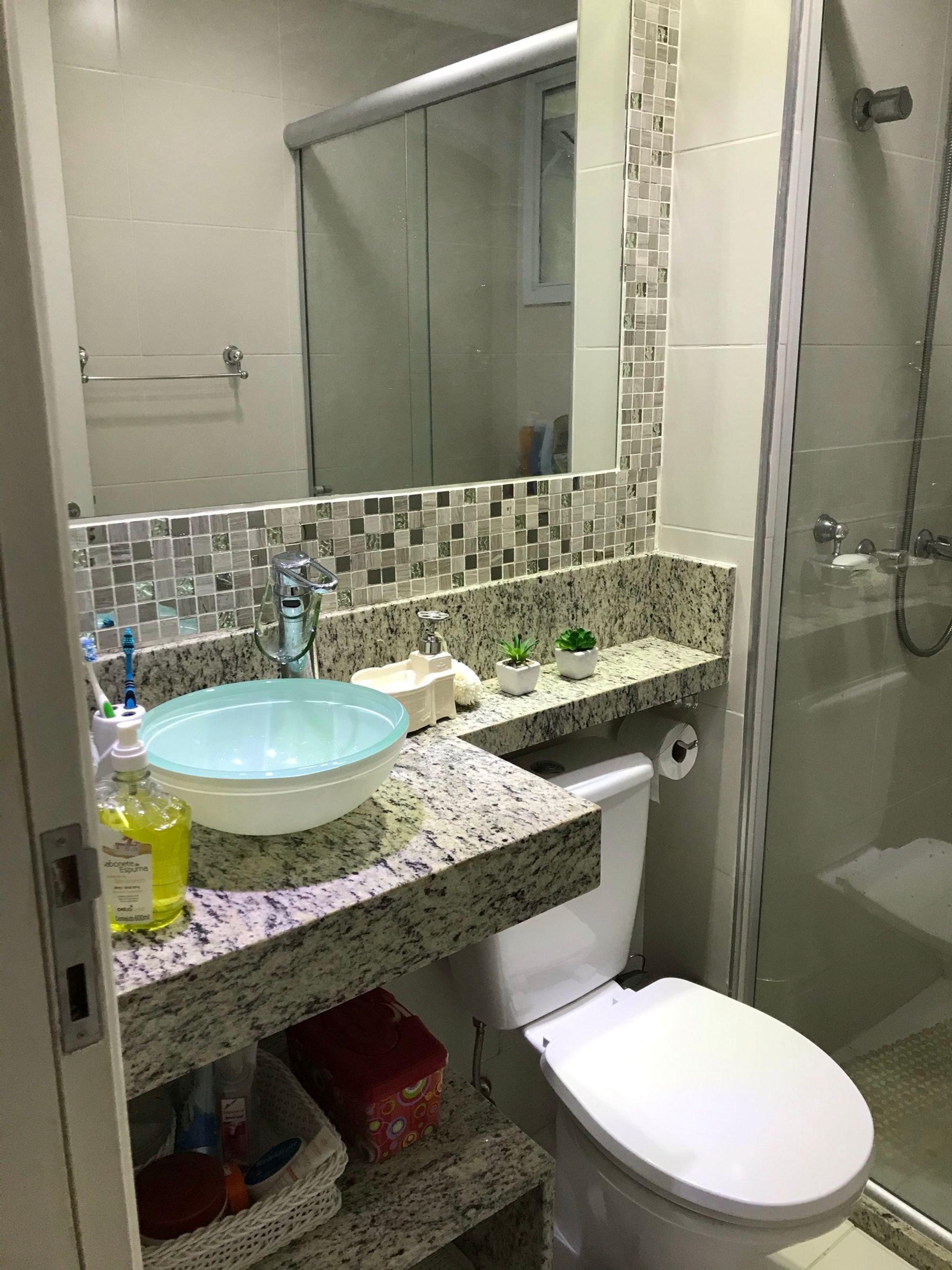 Foto de Banheiro com vaso de planta, escova de dente, vaso sanitário, garrafa, pia